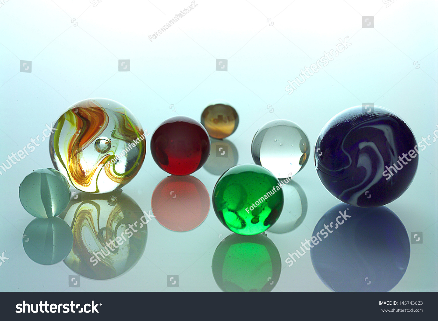 Several Different Colored Glass Balls On Spiegelflaeche Stock Photo 145743623 : Shutterstock