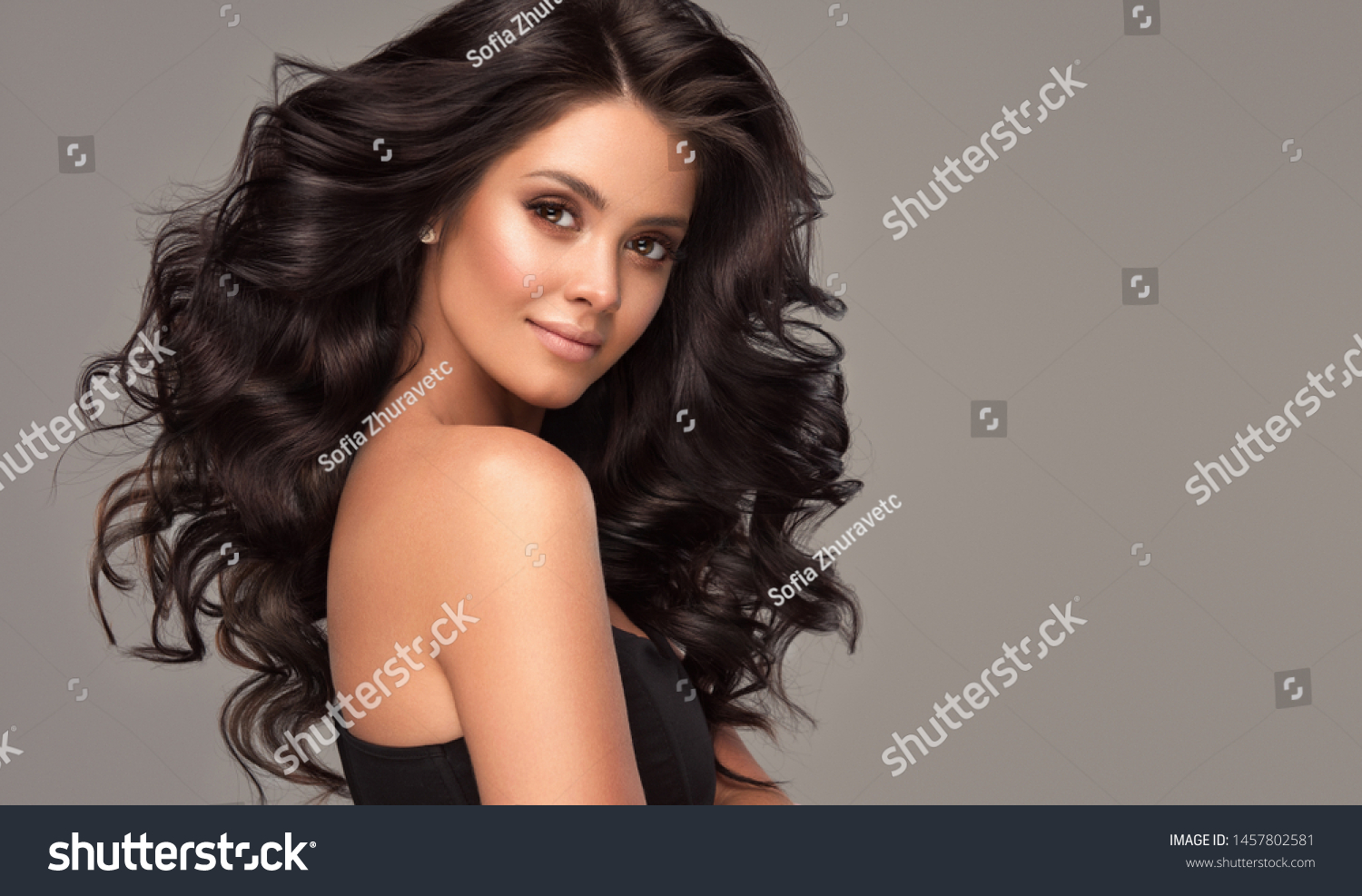 Beauty brunette girl with long  and   shiny wavy black hair .  Beautiful   woman model with curly hairstyle . #1457802581