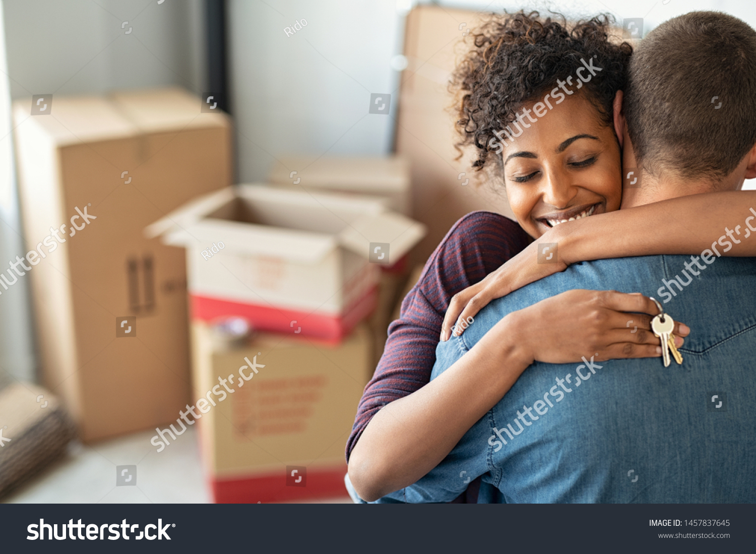 Young african woman holding home keys while hugging boyfriend in their new apartment after buying real estate. Lovely girl holding keys from new home and embracing man. Couple around cardboard boxes. #1457837645