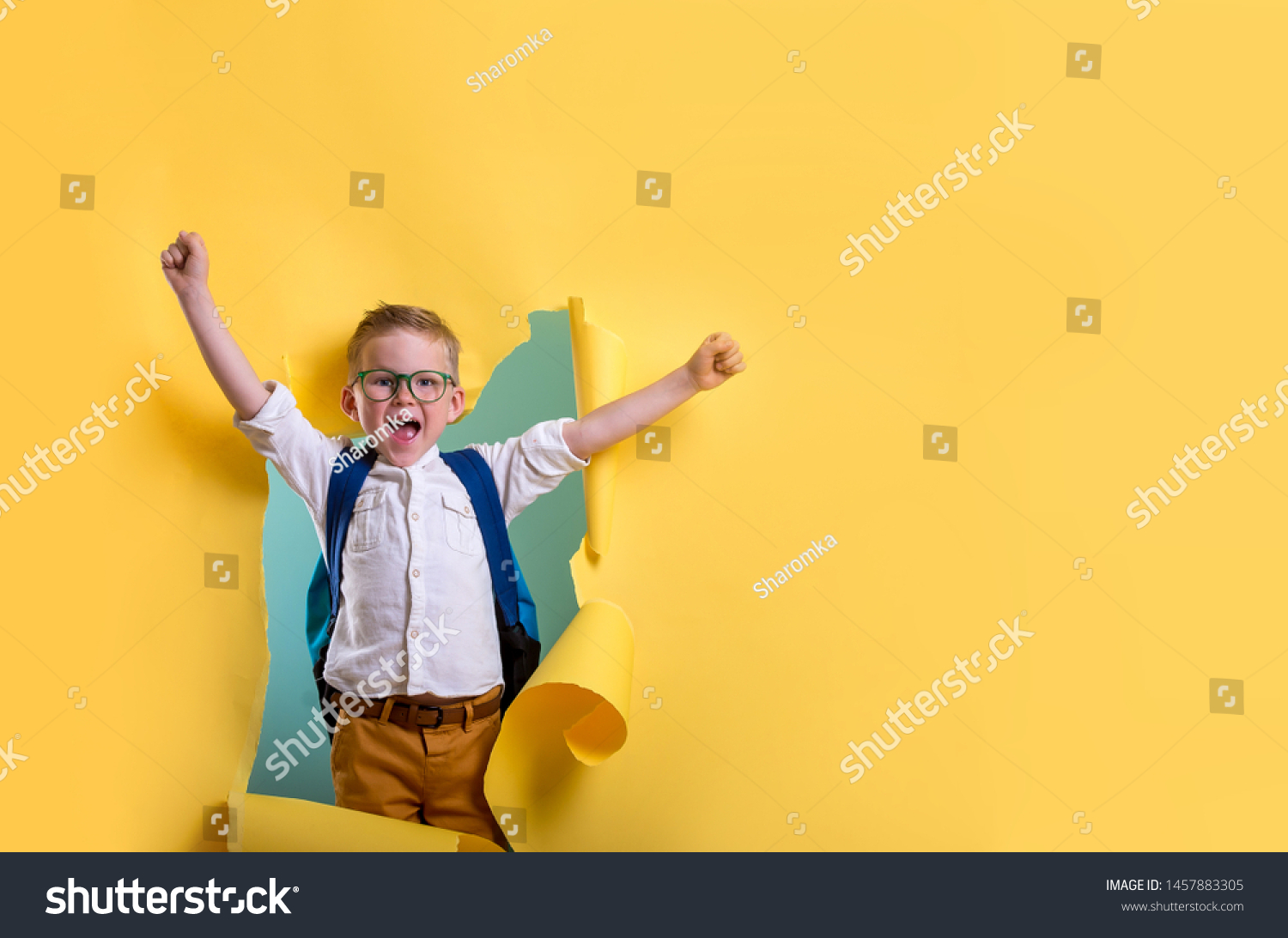 Child boy with book and bag breaking through yellow paper wall. Happy  smiling kid go back to school, kindergarten. Success, motivation, winner, genius concept. Little kid dreaming to be superhero #1457883305