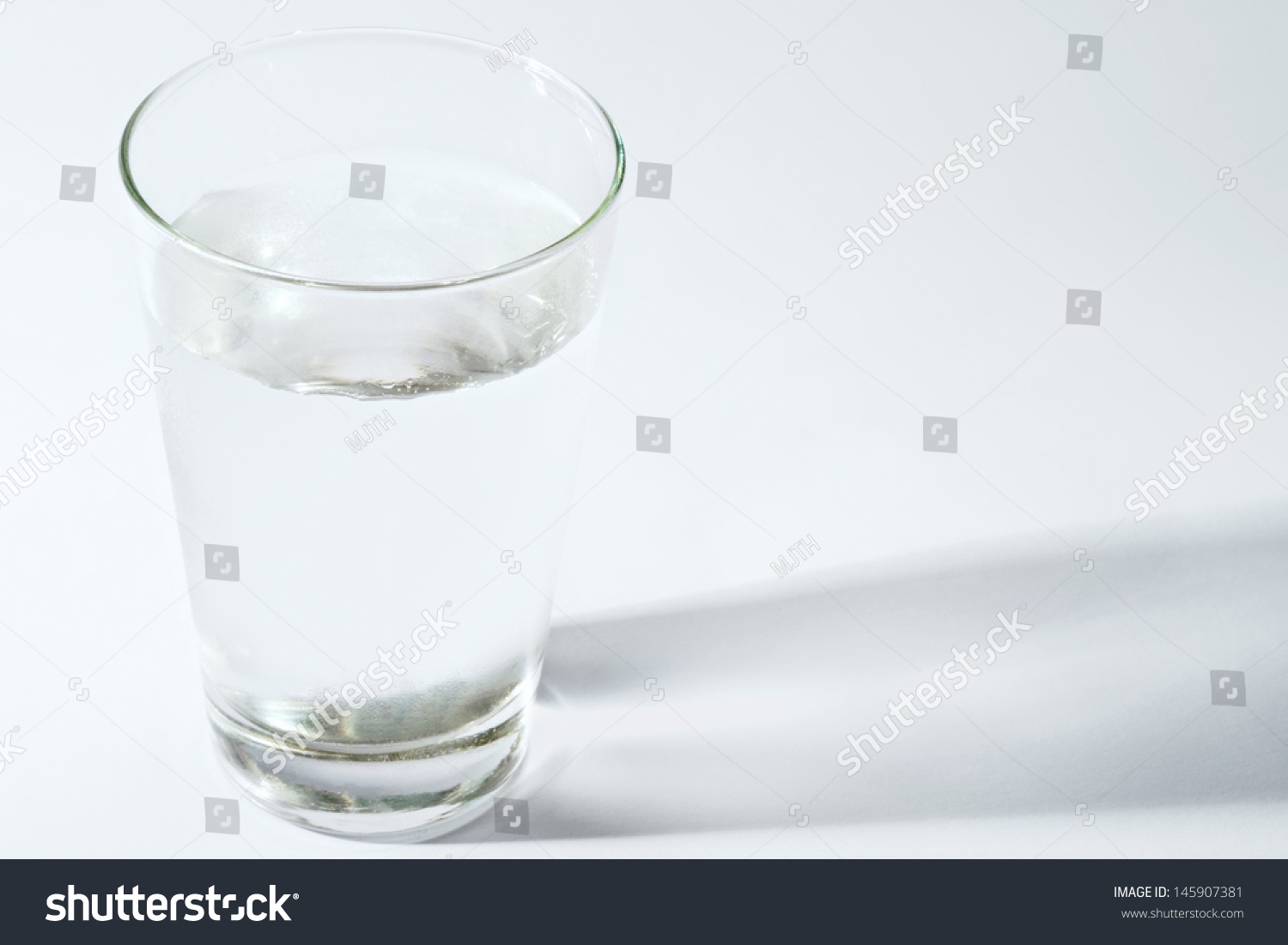 Full glass of clear healthy water standing on a white table with side shadows and space next to it, object. #145907381