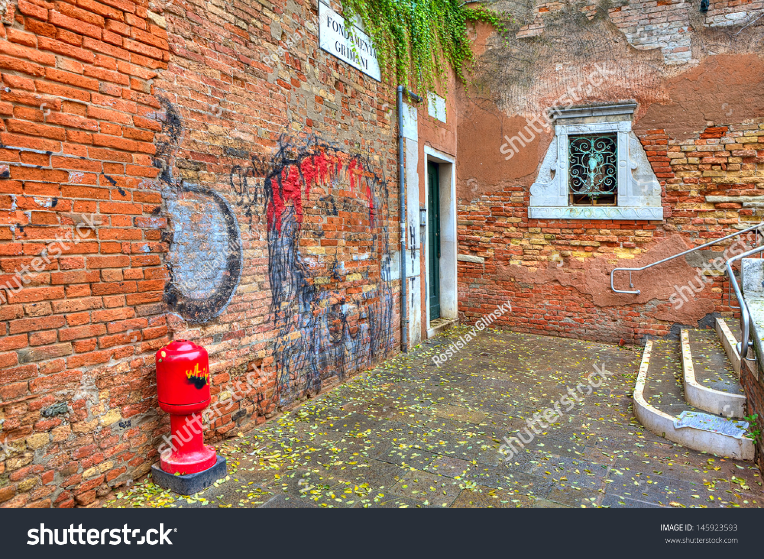 Grafiti wall red - Small Courtyard Among Old Red Brick Walls With Graffiti In Venice Italy