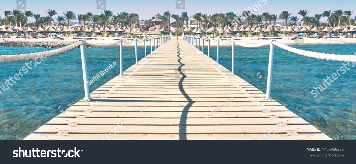 Travel. Pier on the sea. Pier leading to the shore with palm trees.   #1459959296