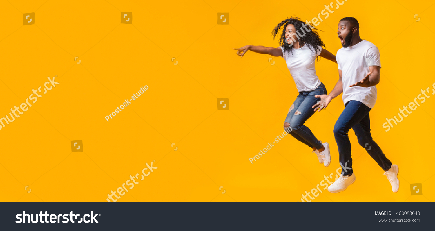 Surprised Black Man Is Looking At Free Space, afro woman is jumping and pointing at empty space, yellow background, panorama #1460083640
