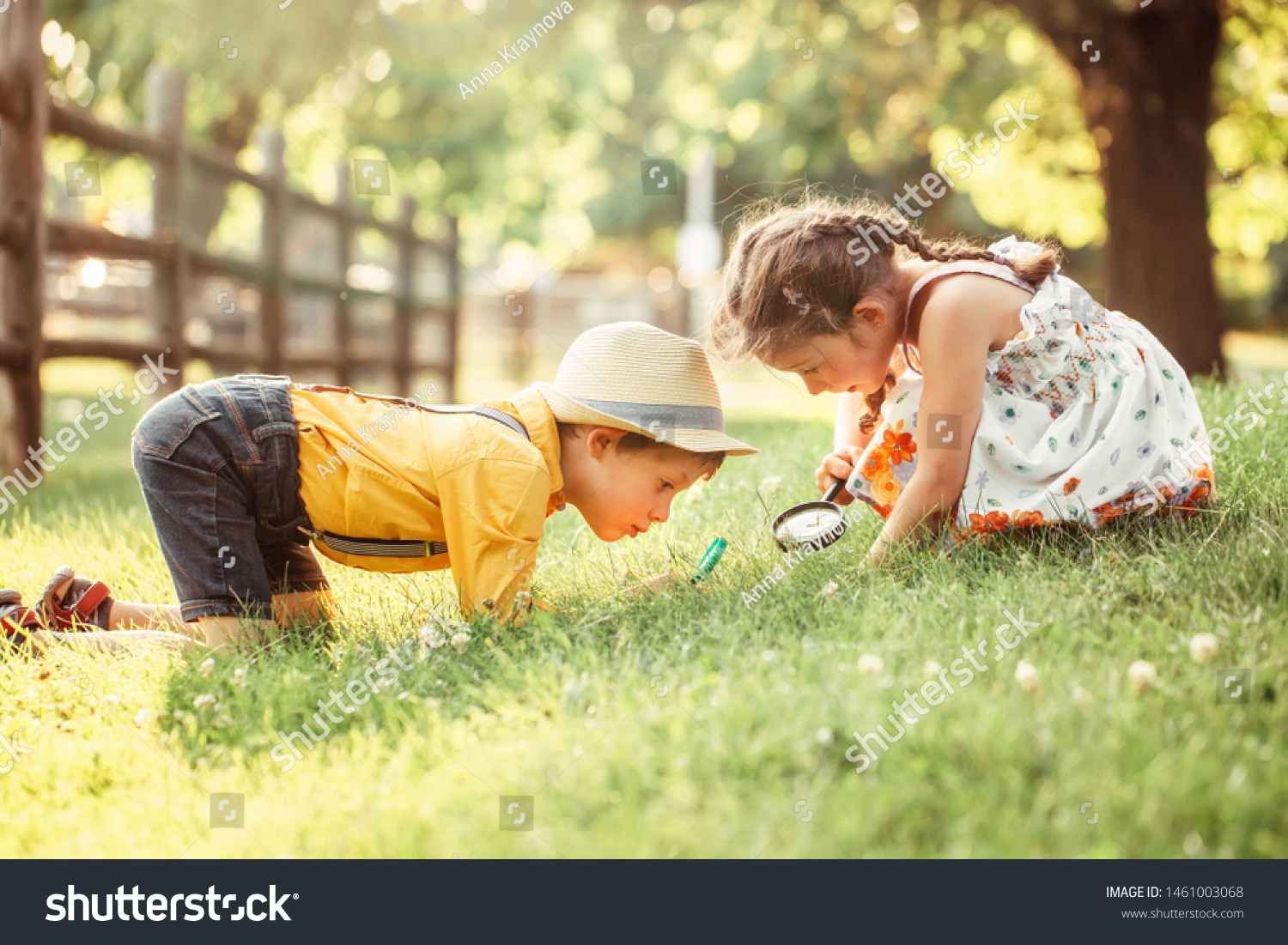 Cute adorable Caucasian girl and boy looking at plants grass in park through magnifying glass. Children friends siblings with loupe studying learning nature outside. Child education concept. #1461003068