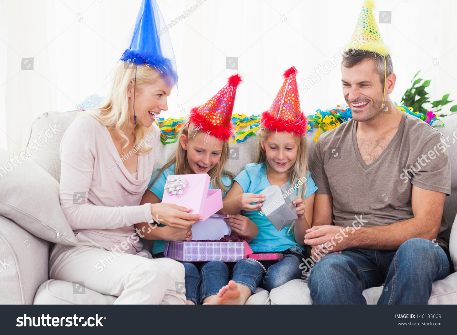 Twins Unwrapping Birthday Gift With Their Parents Sitting On A Couch
