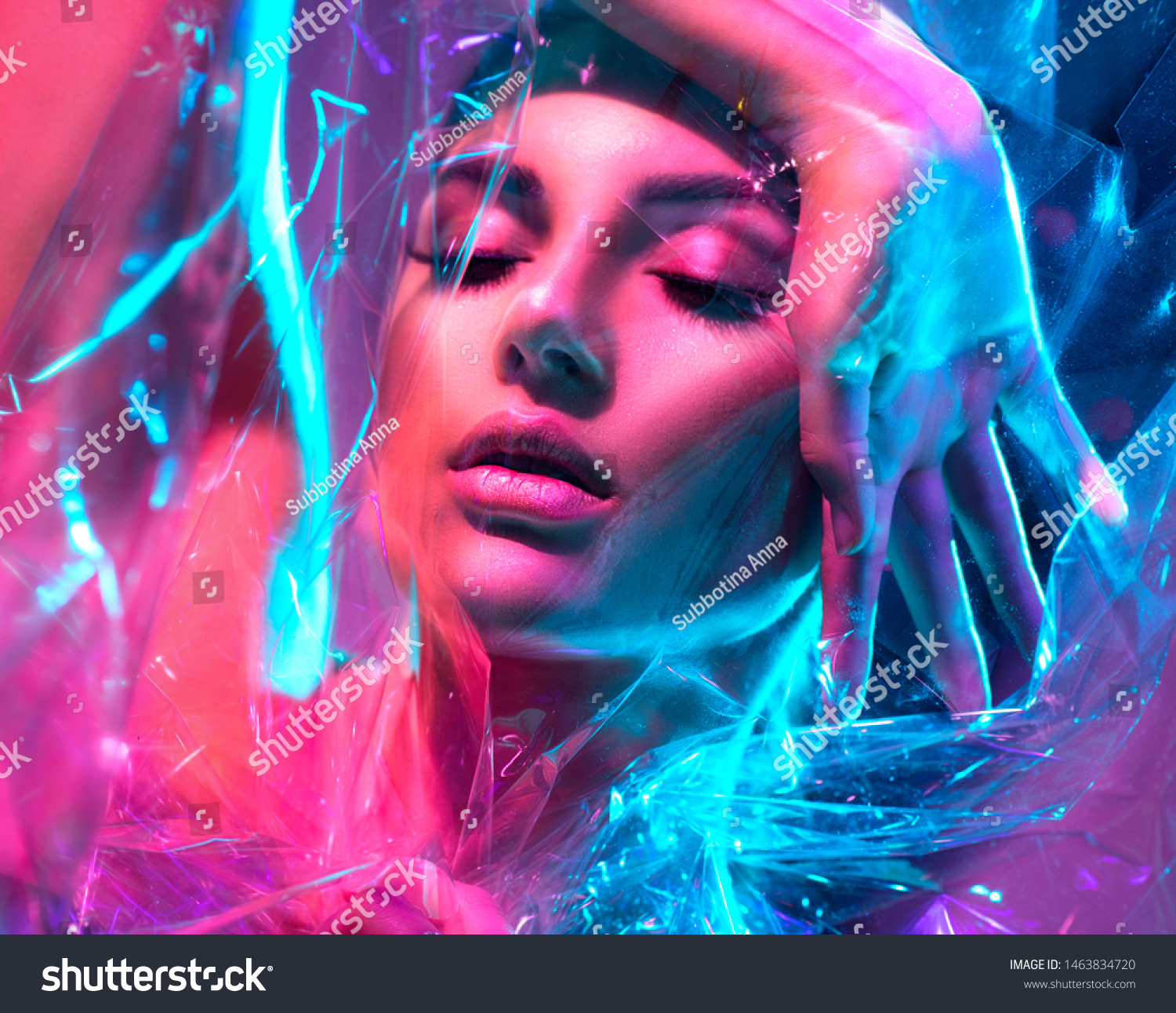 High Fashion model girl in colorful bright neon lights posing in studio through transparent film. Portrait of beautiful sexy woman in UV. Art design colorful make up. On colourful vivid background #1463834720
