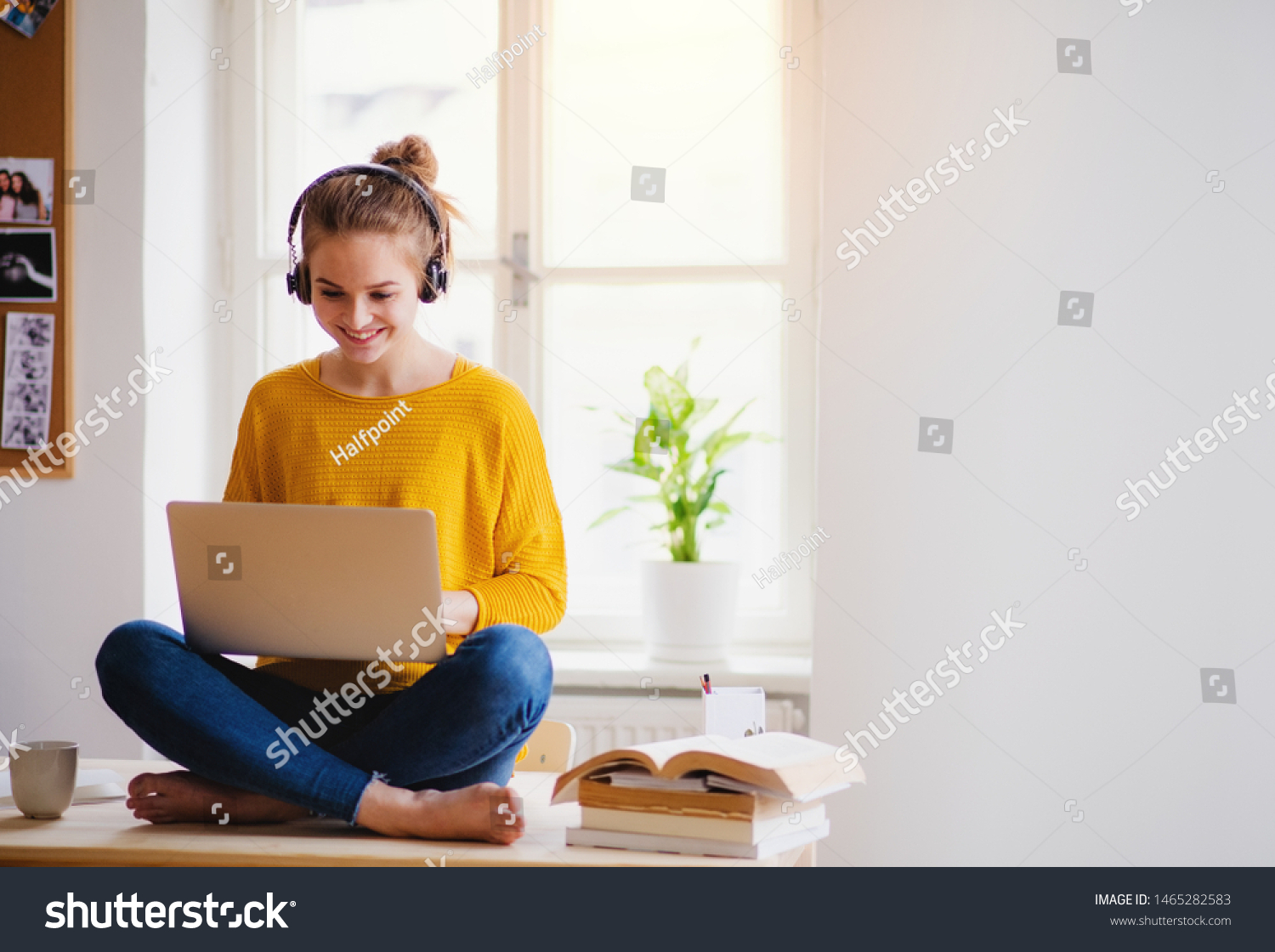 A young female student sitting at the table, using headphones when studying. #1465282583