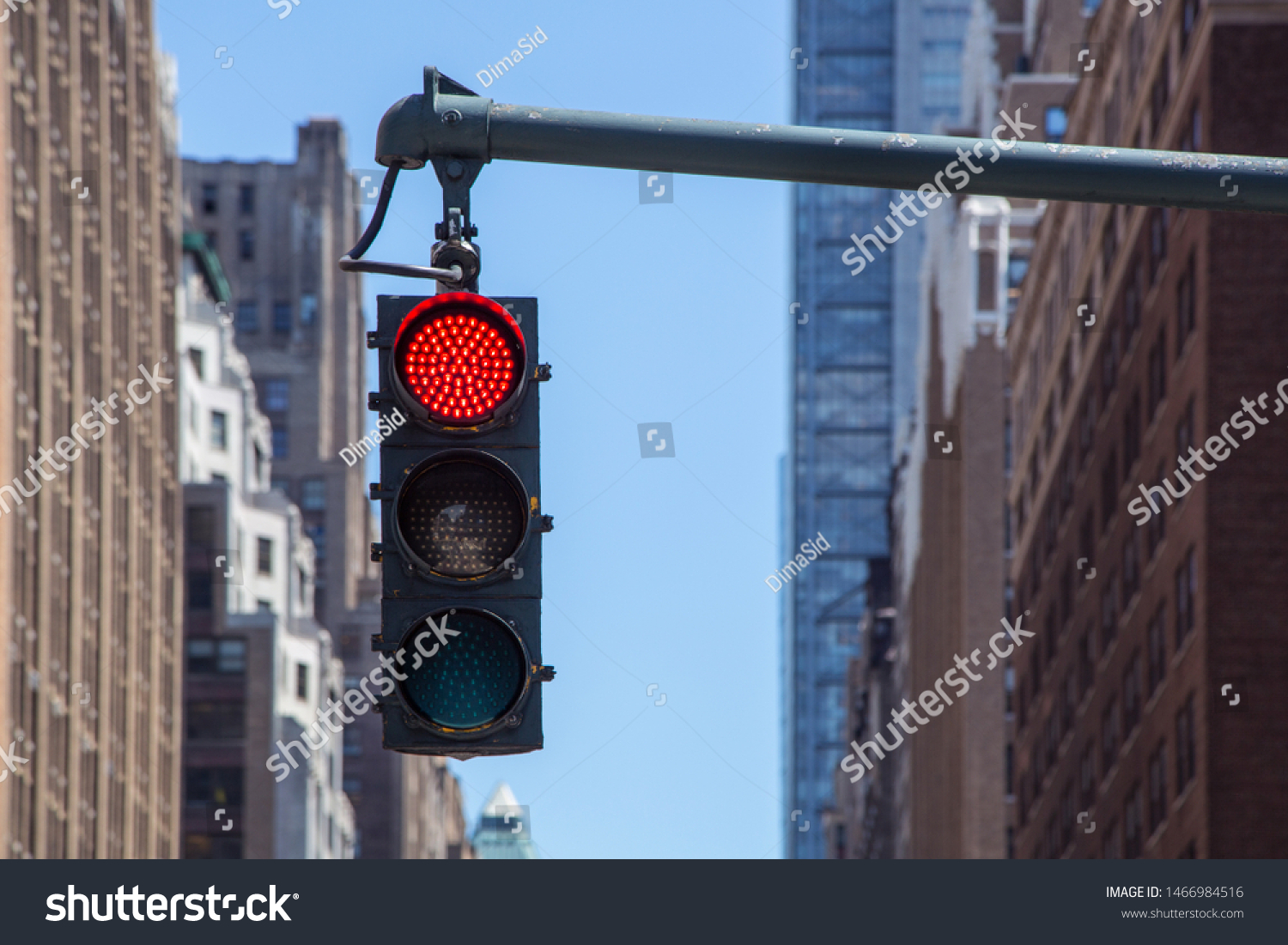 Traffic light closeup with red signal. Traffic light on the background of skyscrapers in New York. Red color traffic light with buildings in the background. Traffic light wallpaper. #1466984516