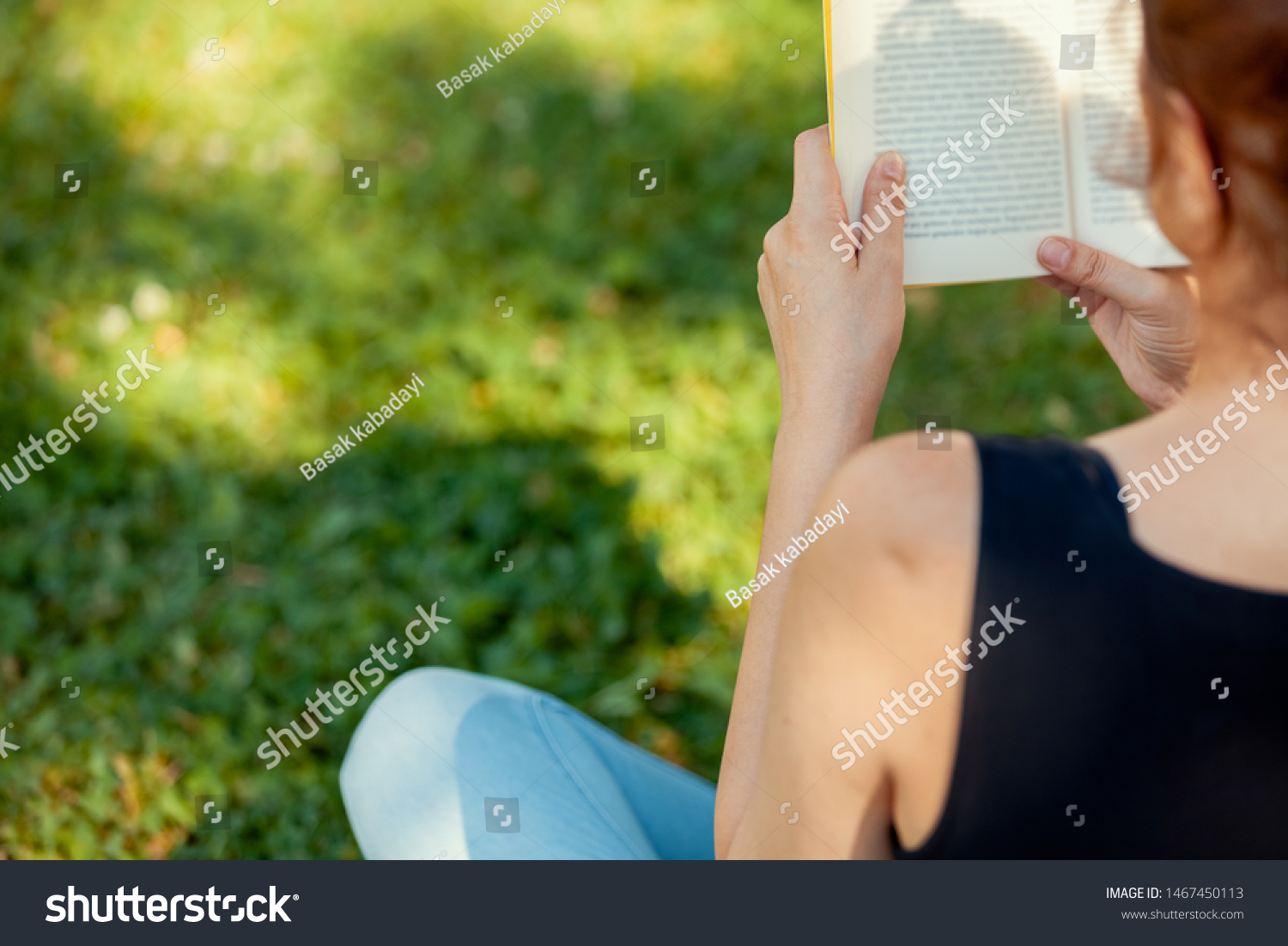 young woman reading and enjoying a book on the bench in public park. closeup backview photo of young woman reading book.  #1467450113