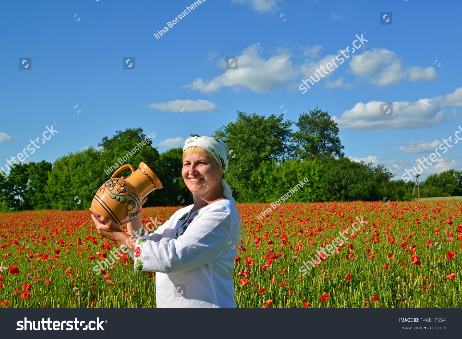 The rural woman drinks water from a jug in a poppy field