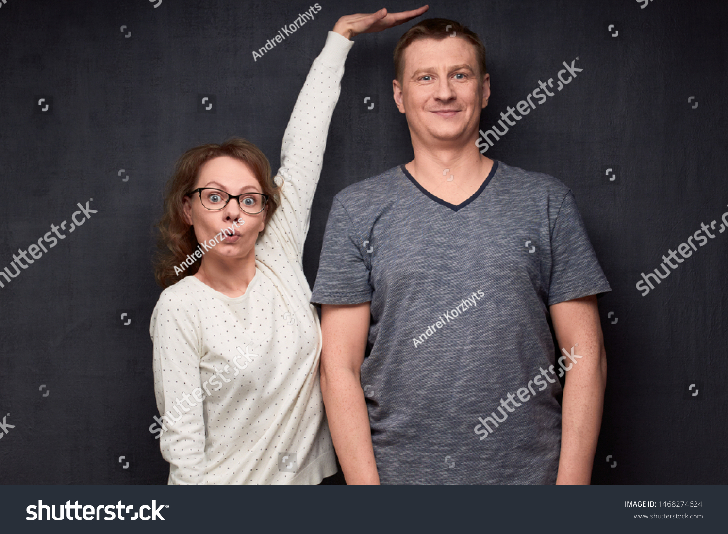 Studio waist-up shot of amazed short woman pulling up and showing with hand at height of tall man standing beside her, smiling and looking at camera, over gray background. Variety of person's heights