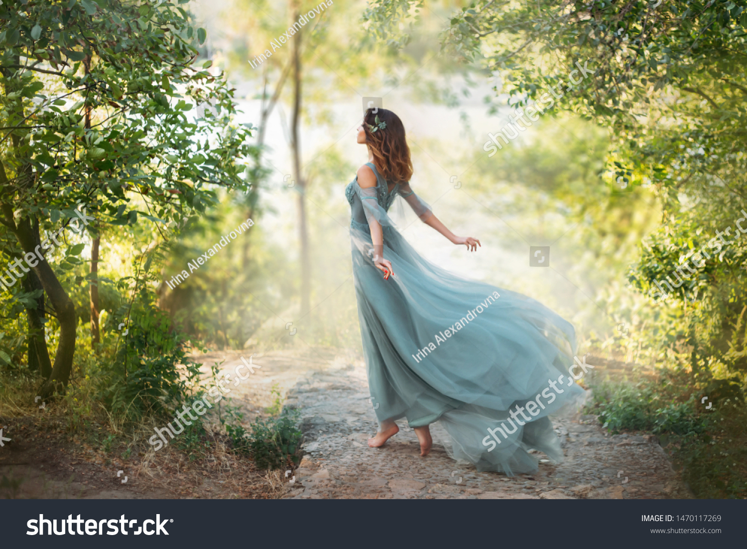 fairy-tale princess in light summer blue turquoise dress on wide path and walks towards wind, graceful dancing girl in image of flower with flying long hem of dress, nymph of bright green forest #1470117269