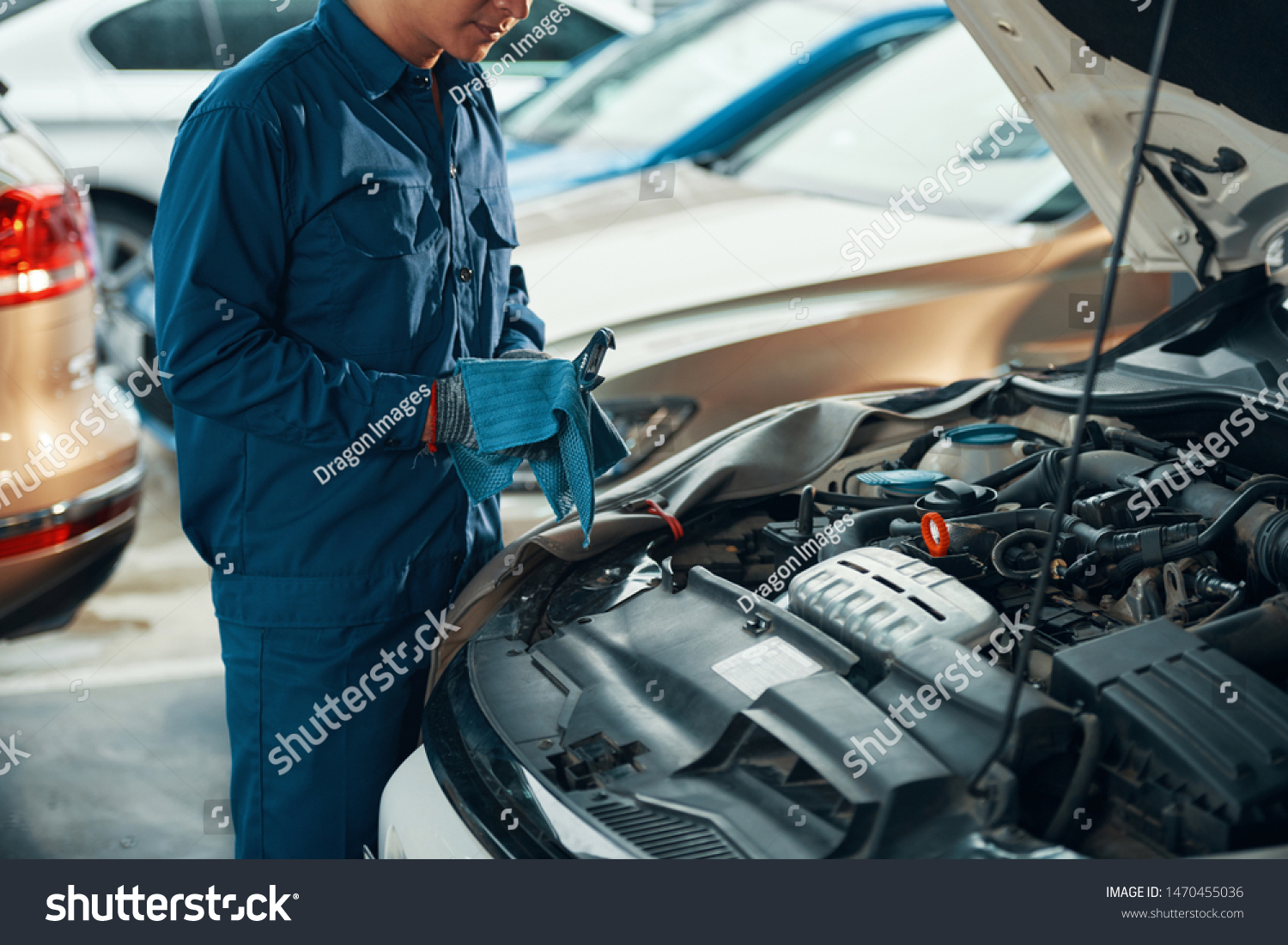 Cropped image of mechanic in uniform wiping wrench with clean cloth after working #1470455036