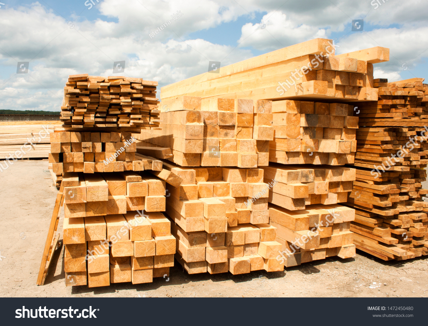 Lumber warehouse in the open air. Wooden beam, planks of wood, stacked in stacks. Sunny day, blue sky with clouds. Horizontal photo #1472450480