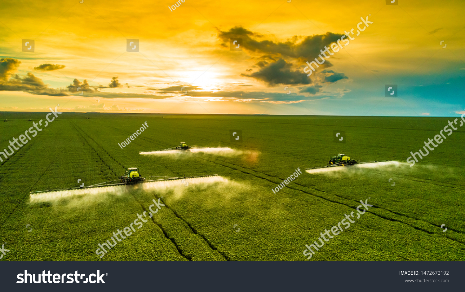 Agricultural sprayers making application at the end of the day with beautiful sunset