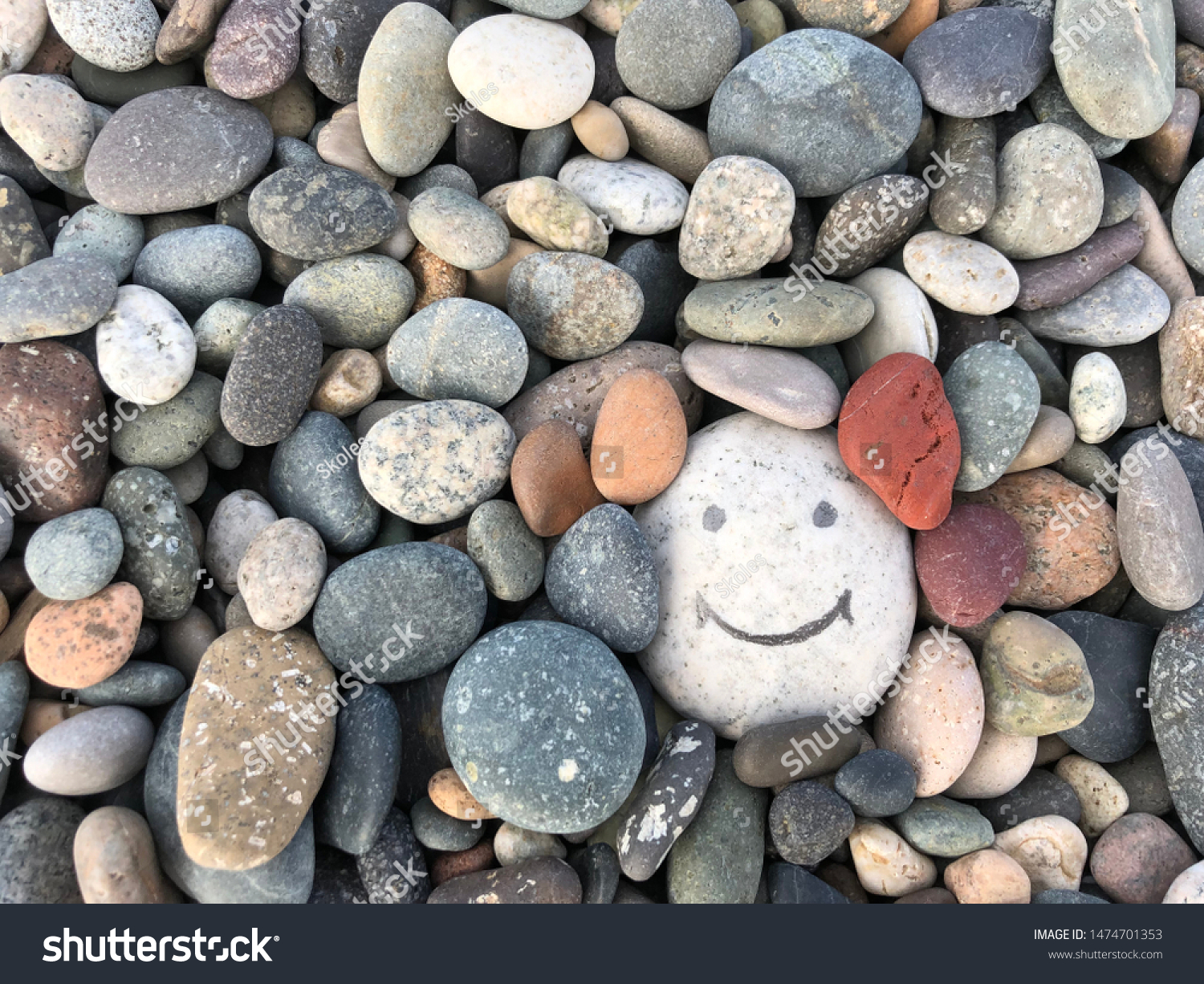 Stone with a painted smile. On the shore, one stone stands out from the others. On a small stone is an image of a happy face. Concept: joy, happiness, positive, kindness. #1474701353