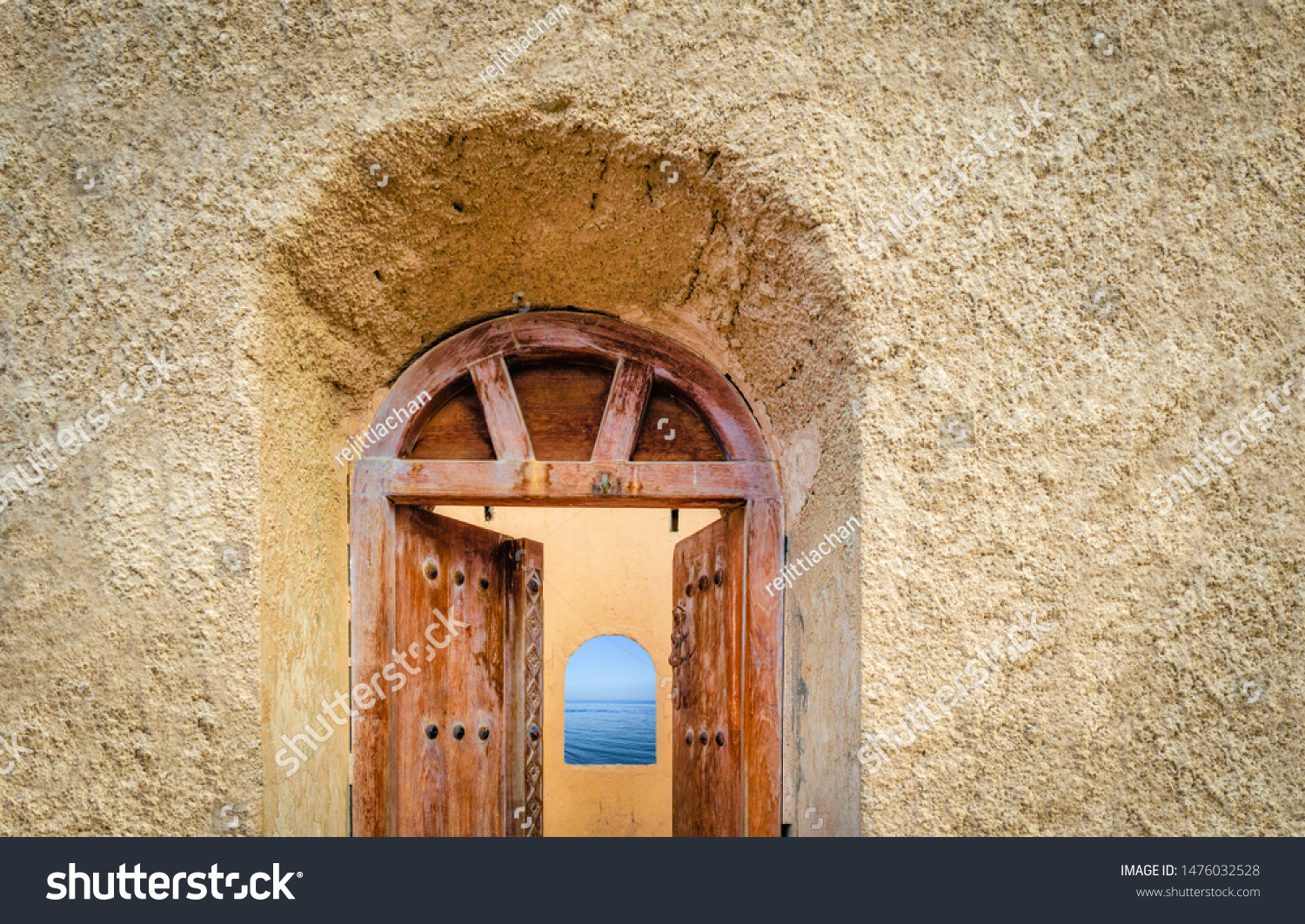 Old, antique door of a watchtower opening to reveal a arch window to the sea. From Muscat, Oman.
