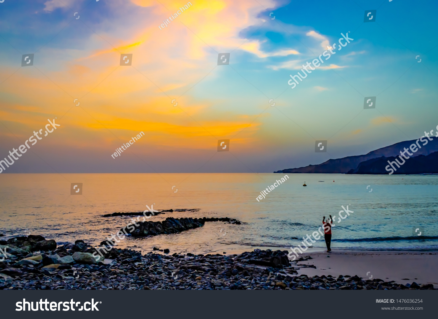 Man doing a yoga pose facing a beautiful sky in the morning on the beach. From Muscat, Oman.