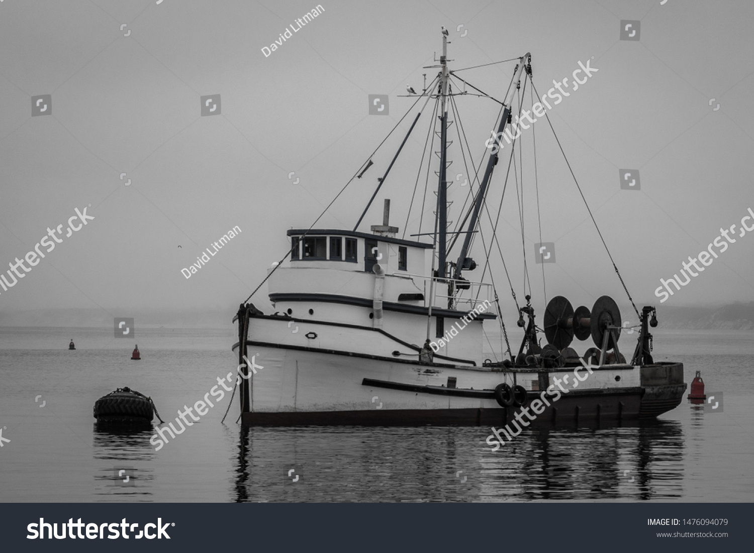 Black and white image of an old fishing boat moored in the Monterey Harbor and Marina along the Monterey Bay of central California.