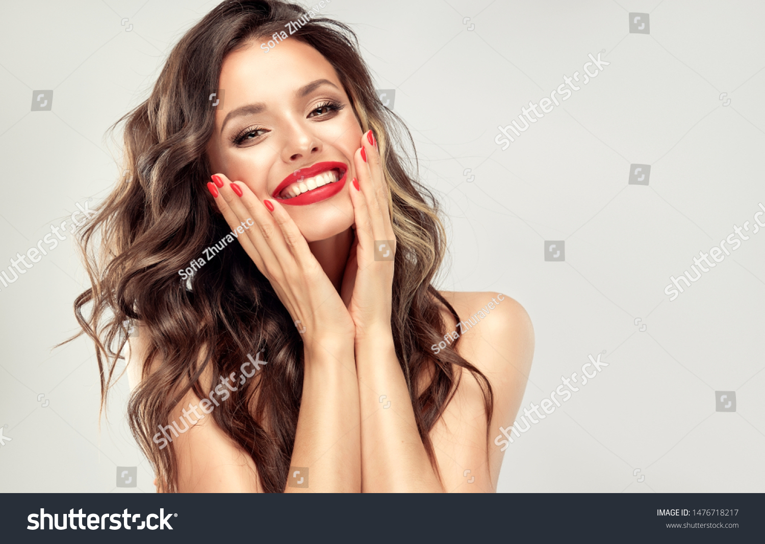 Beautiful laughing brunette model  girl  with long curly  hair . Smiling  woman hairstyle wavy curls . Red  lips and  nails manicure .    Fashion , beauty and make up portrait  #1476718217