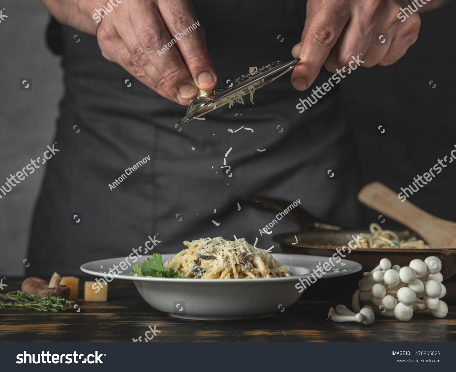 Chef hands cooking Italian pasta and adding cheese parmesan in dish on wooden table background. #1476805823