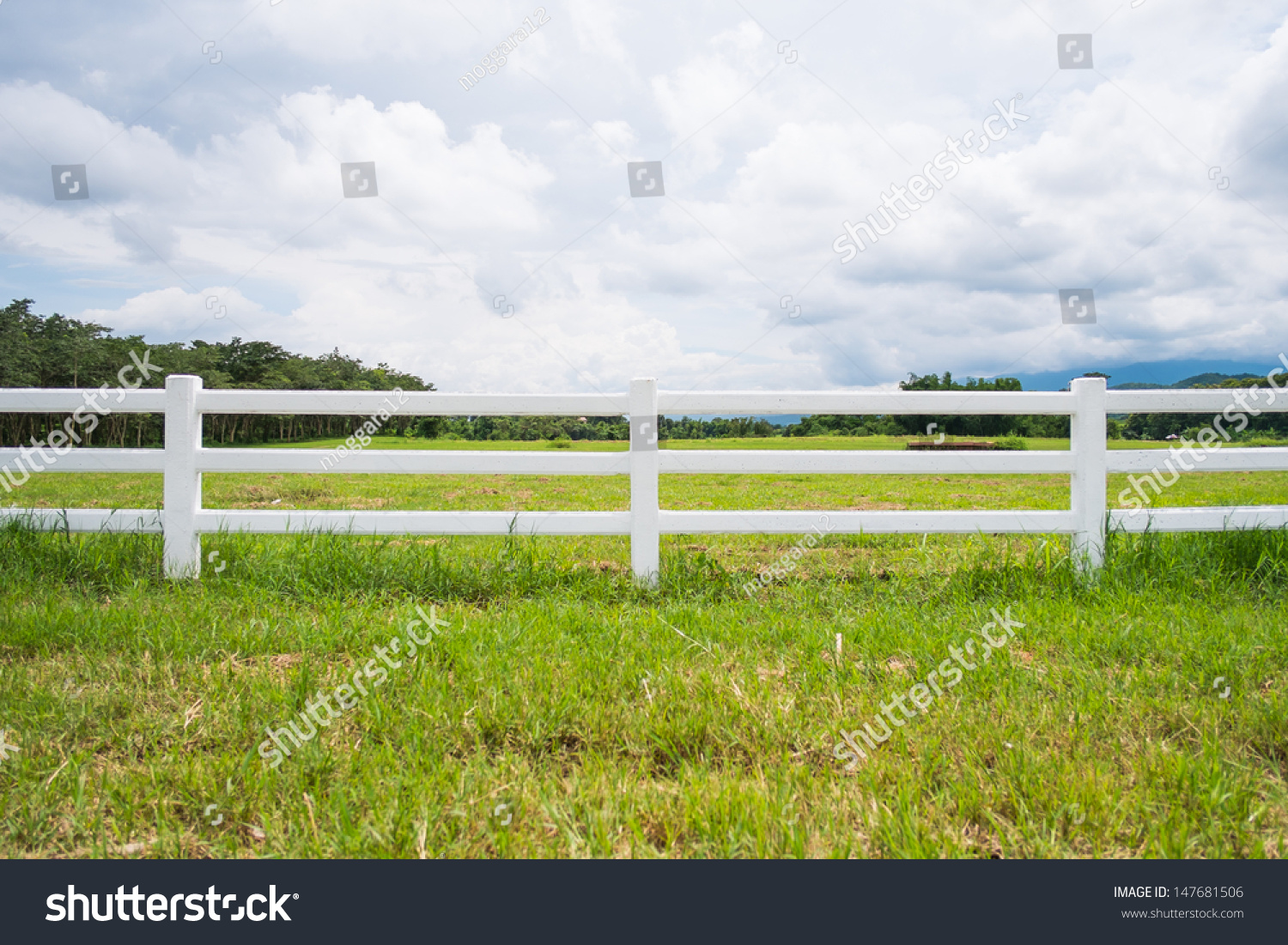 White Fence In Farm Field And Overcast Sky Stock Photo