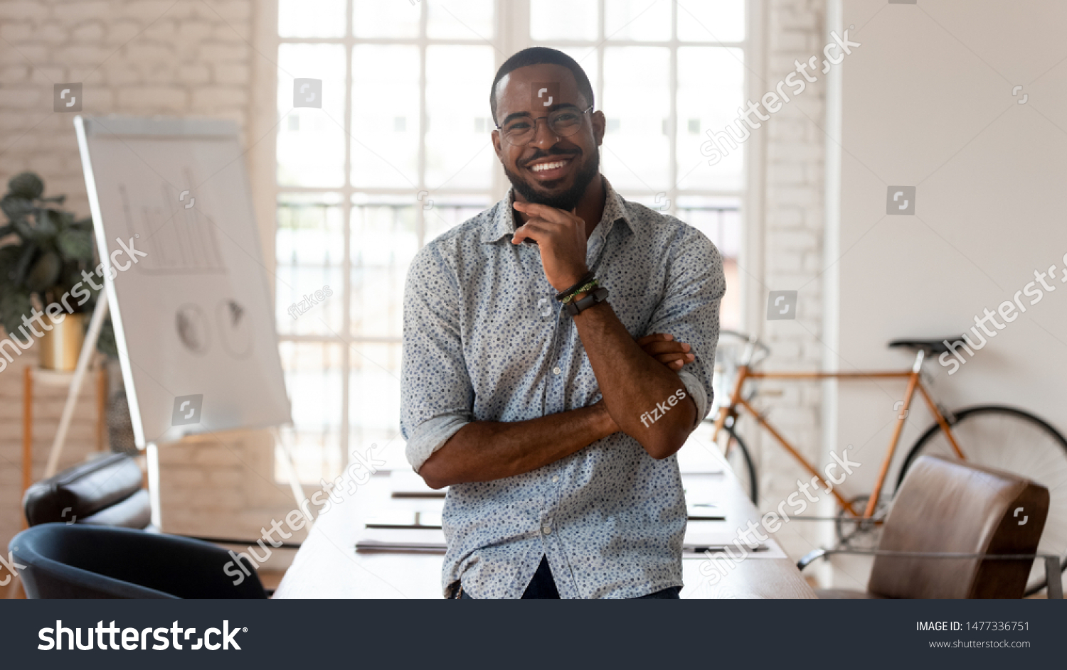 Happy african american businessman entrepreneur startup owner stand in modern office looking at camera, smiling young black designer creative occupation person posing in work space, business portrait #1477336751