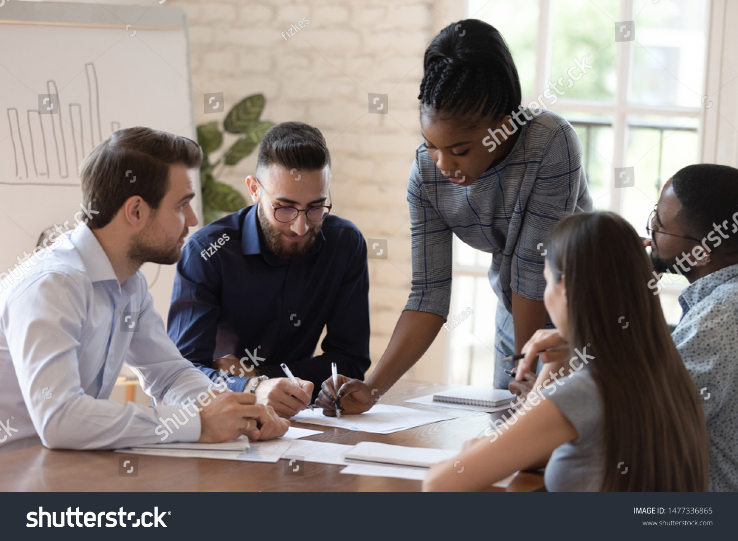 Serious african woman supervisor boss teach diverse staff workers explain project plan paperwork at group meeting, focused black female mentor training business team at corporate office briefing #1477336865
