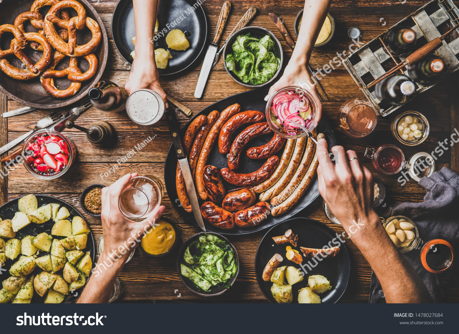 Flat-lay of Octoberfest party dinner table with grilled meat sausages, German pretzel pastry, potatoes, cucumber salad, sauces, beers and peoples hands with food over dark wooden background, top view #1478027684