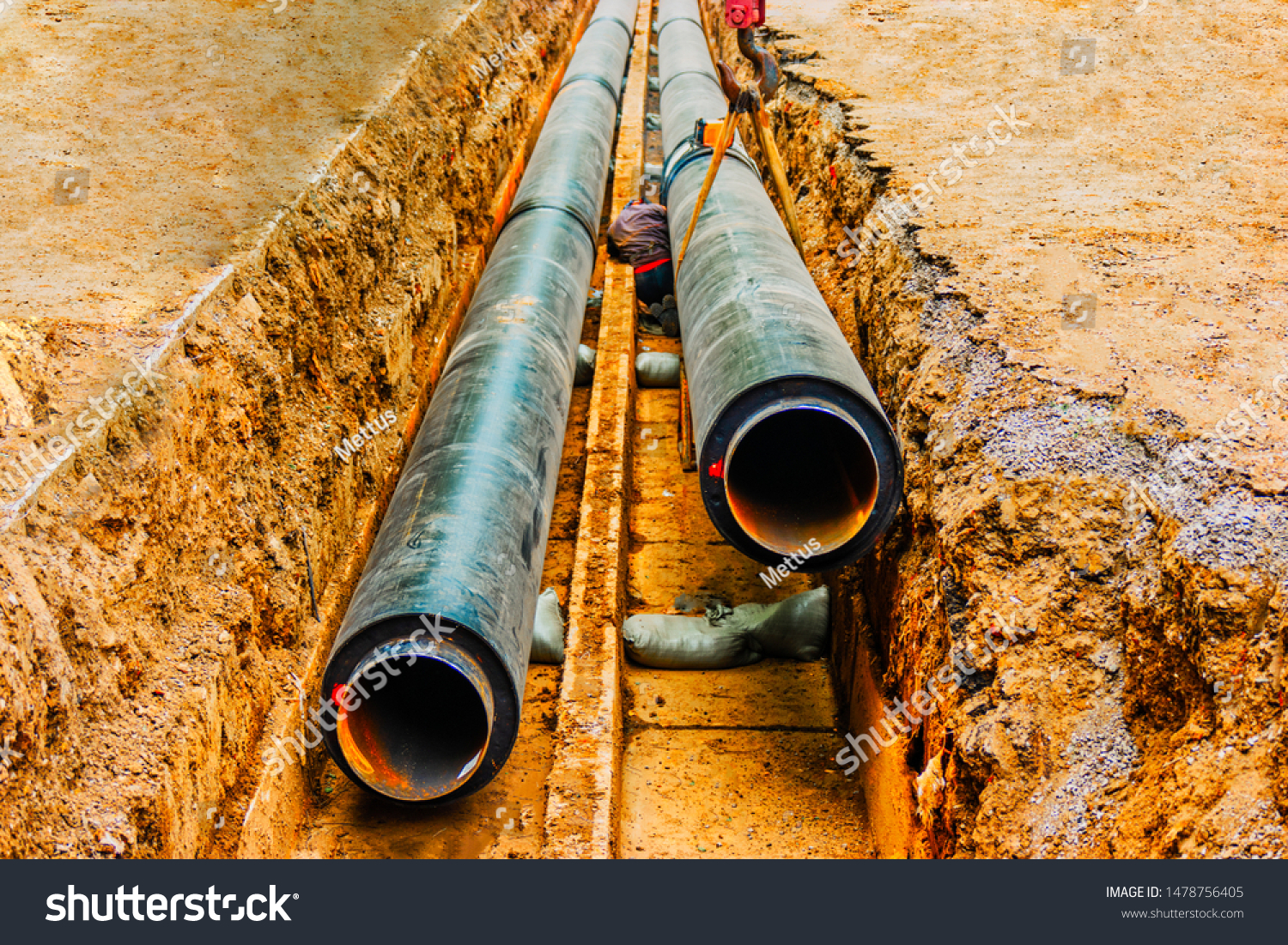 Underground pipe being fixed in trench. Man do a circular welding in trench