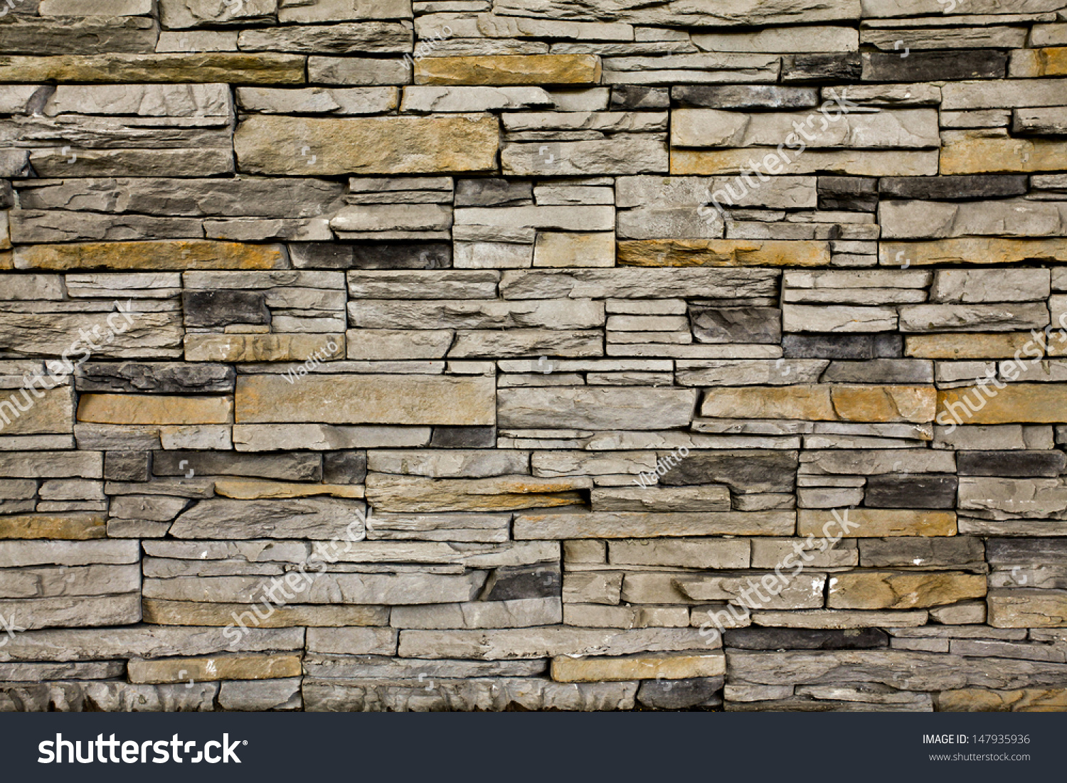 Grungy textured red and yellow stone wall inside old neglected and deserted  interior, masonry and