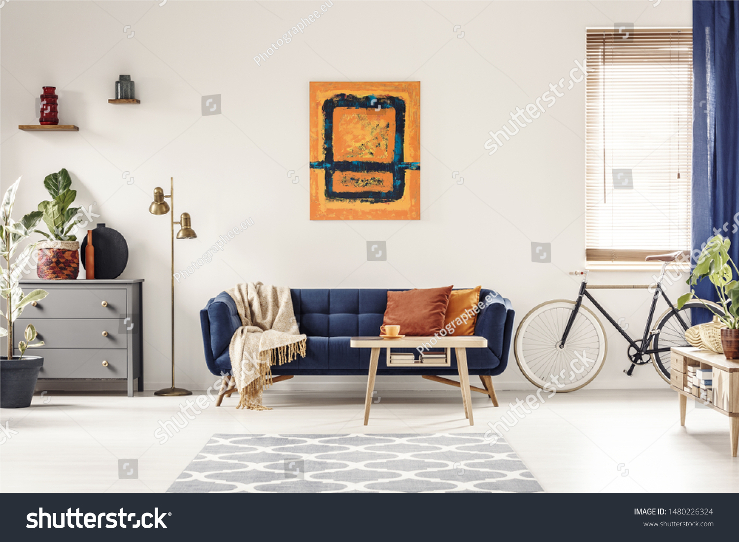 Yellow and blue painting hanging on white wall in bright living room interior with grey cupboard, gold lamp, sofa with blanket and pillows, and bike standing under window with blinds #1480226324