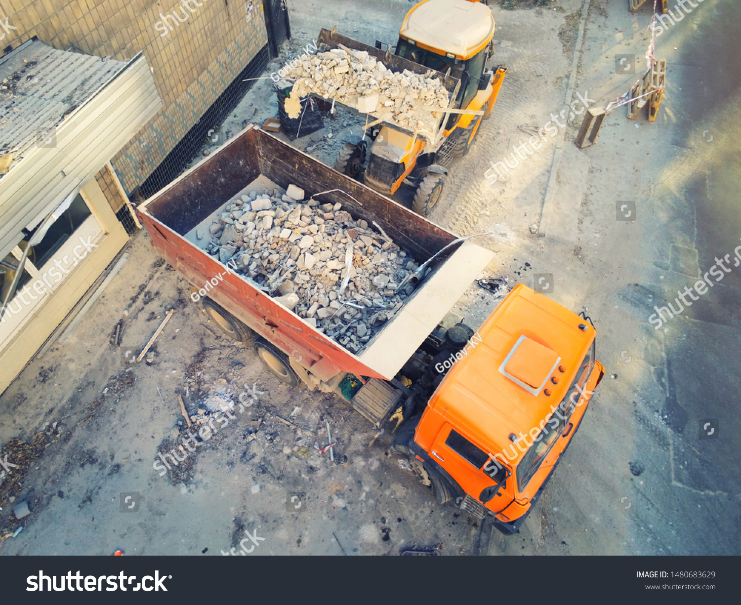 Bulldozer loader uploading waste and debris into dump truck at construction site. building dismantling and construction waste disposal service. Aerial drone industrial background #1480683629