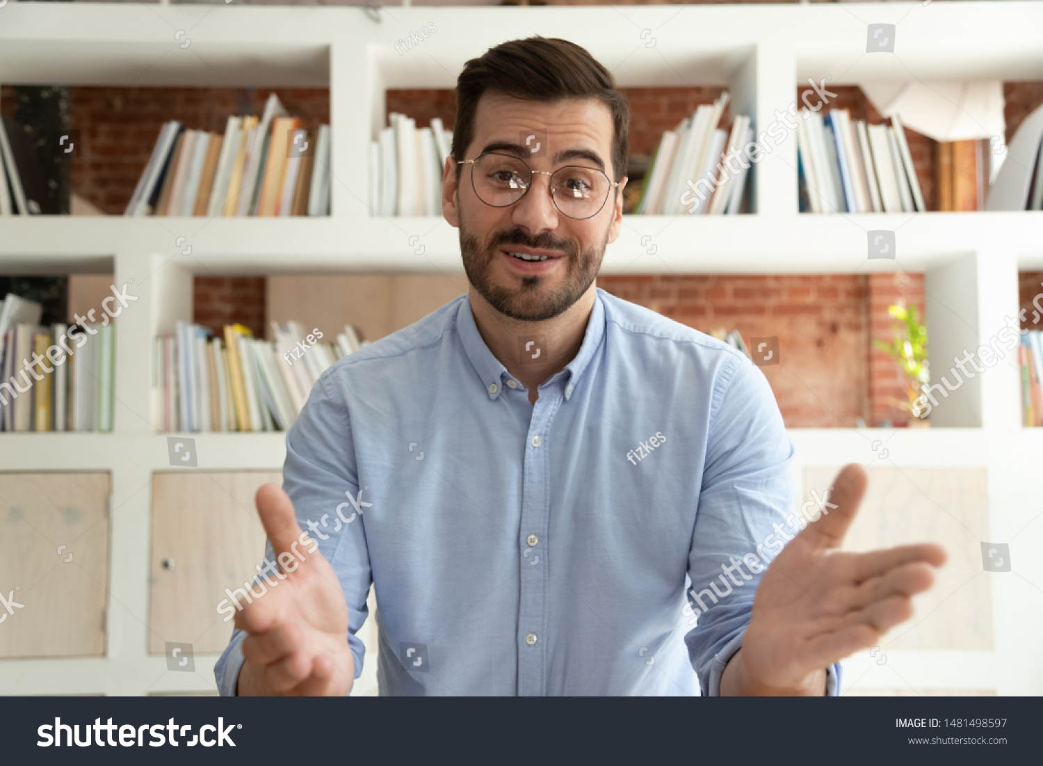 Smiling young businessman sit at desk talk on webcam having video call or conversation with client, motivated millennial male coach or trainer speak shoot online tutorial, record training course #1481498597