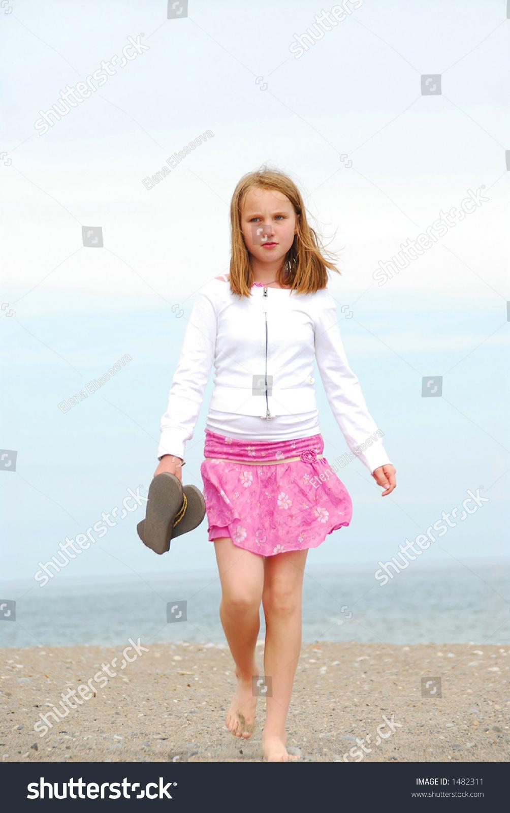 Young Pre Teen Girl Female Woman Torso Vertical Format: Young Preteen Girl Walking On A Sandy Beach Stock Photo