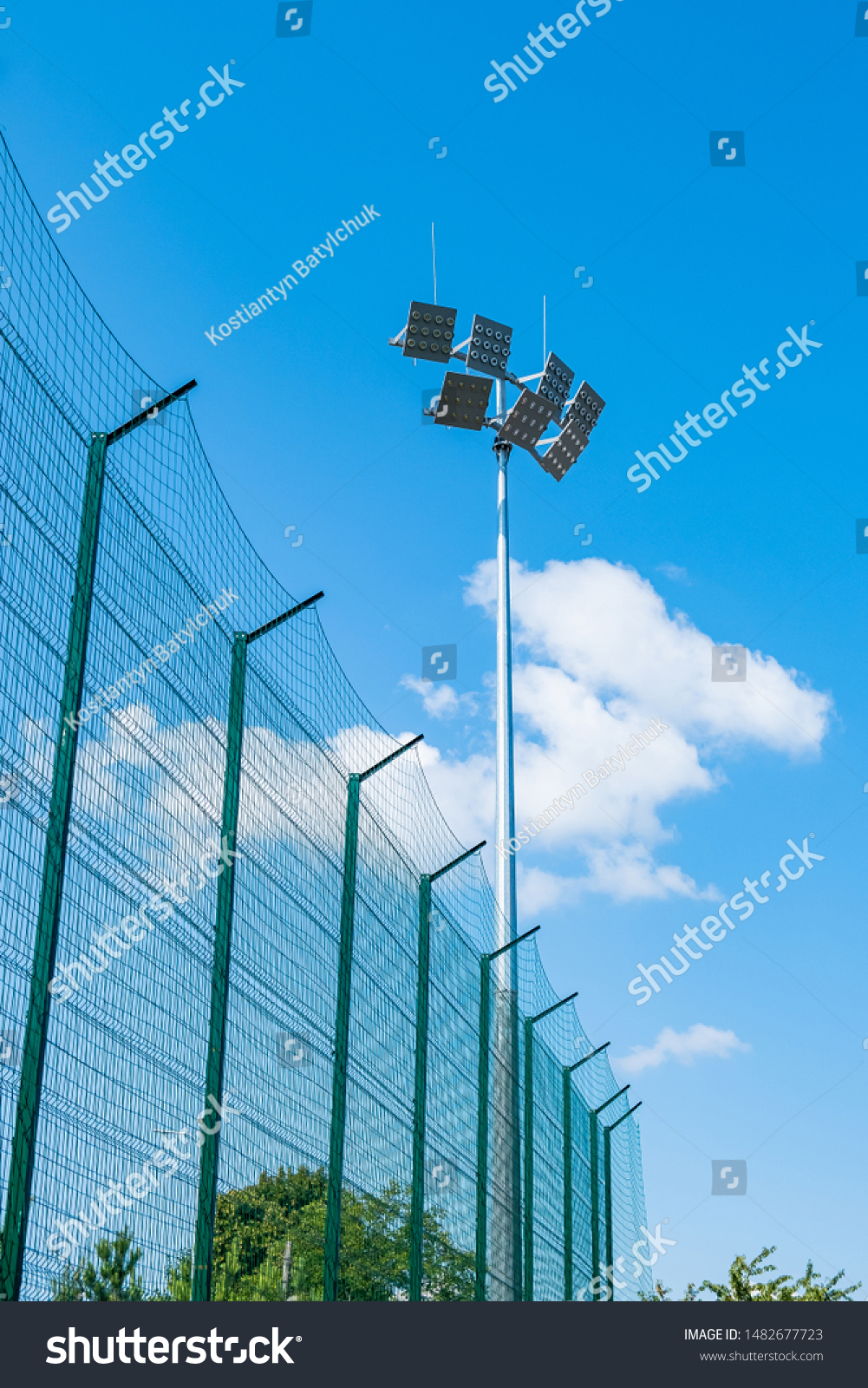 Tall pillar with spotlights to illuminate a football stadium against the sky with clouds  and protective mesh #1482677723