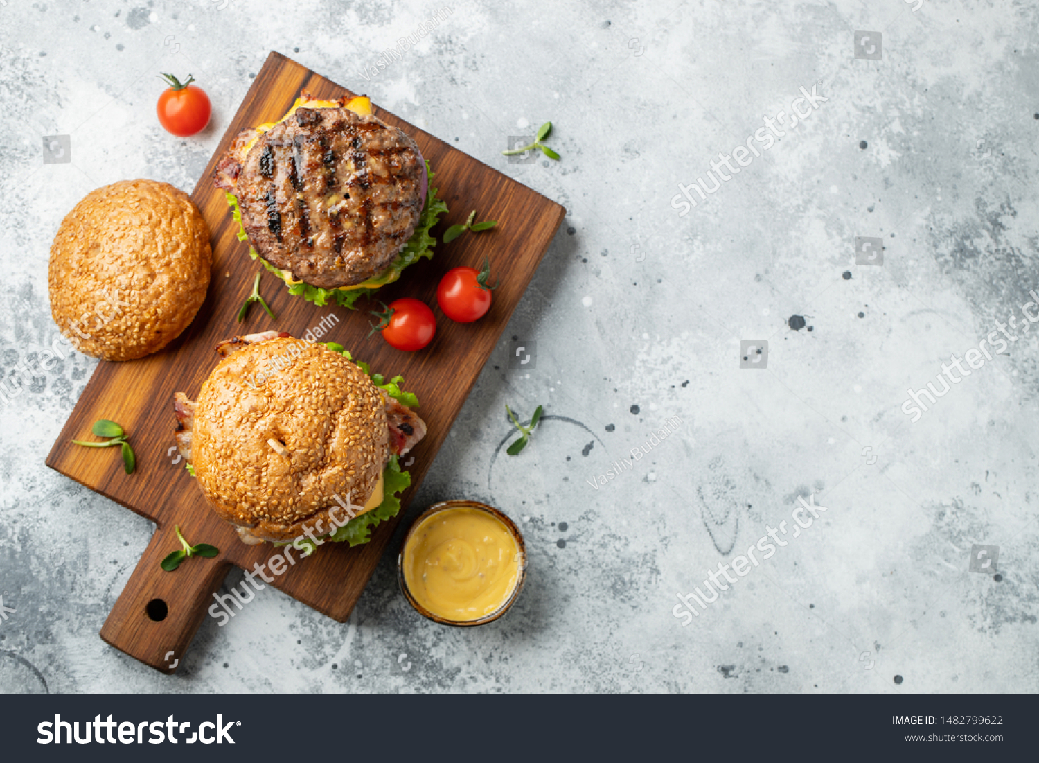 Tasty grilled home made burger with beef, tomato, cheese, bacon and lettuce on a light stone background with copy space. Top view. fast food and junk food concept. Flat lay #1482799622