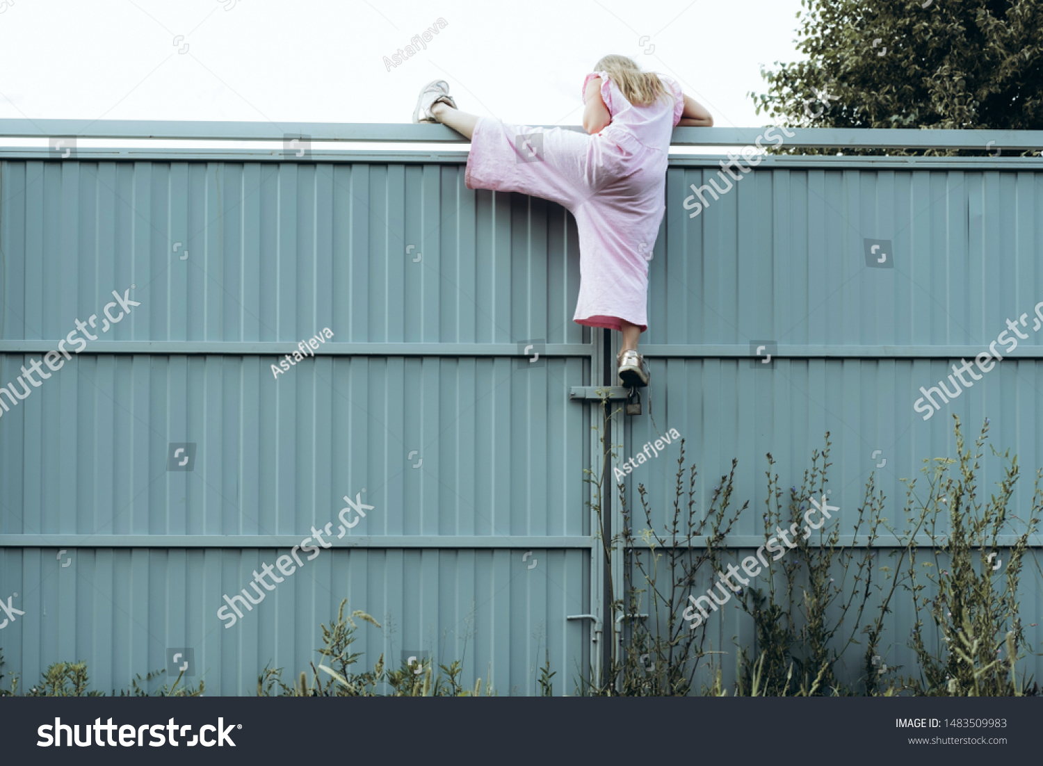 Girl climbing metal fence outdoor. Curious child on high white painted gates. Naughty kid playing outside, breaking rules. Childhood and youth concept. Restless teen entering private property #1483509983