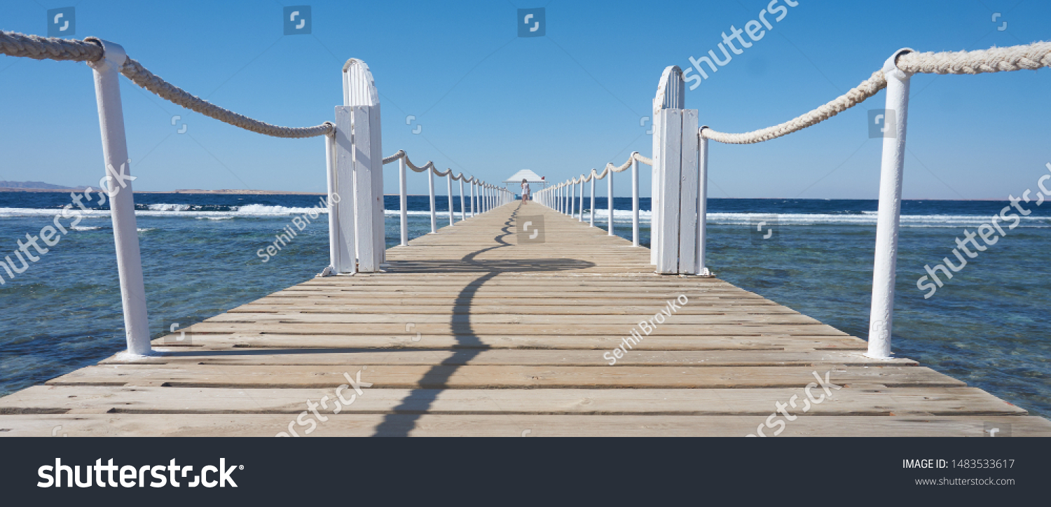 Pier on the seashore, with a girl walking along the pier into the distance. Travel.         #1483533617