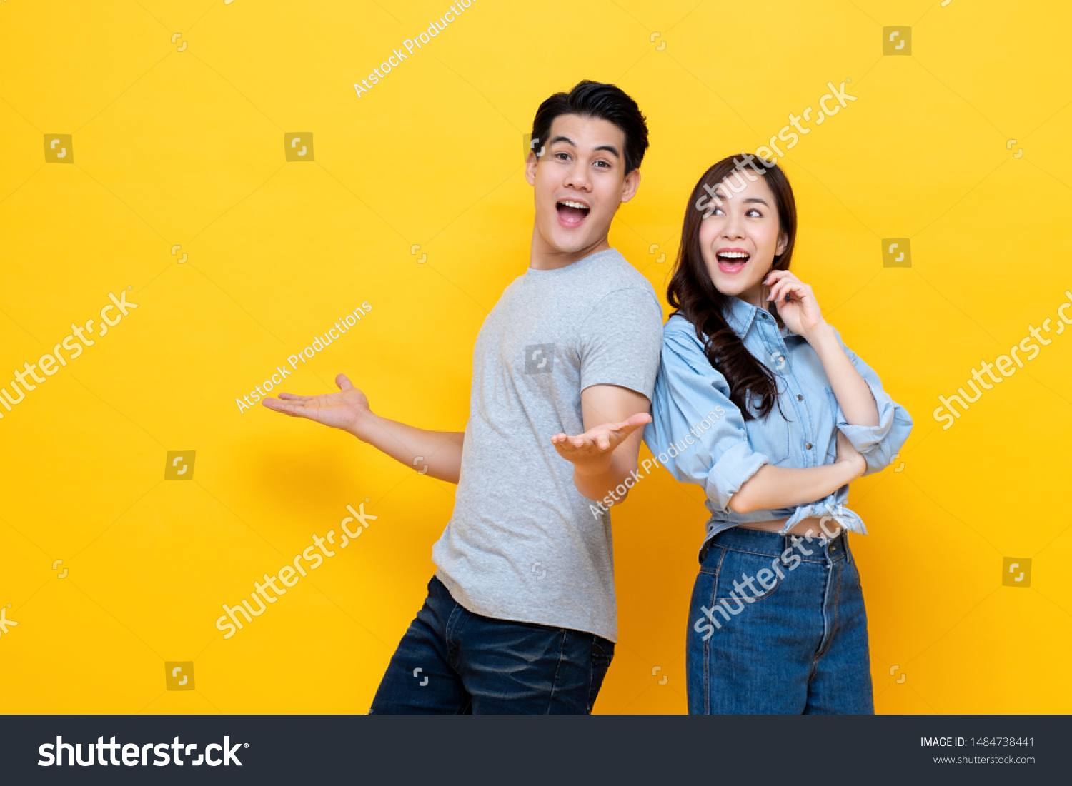 Attractive smiling young Asian couple being happy and amazed isolated on yellow studio background #1484738441