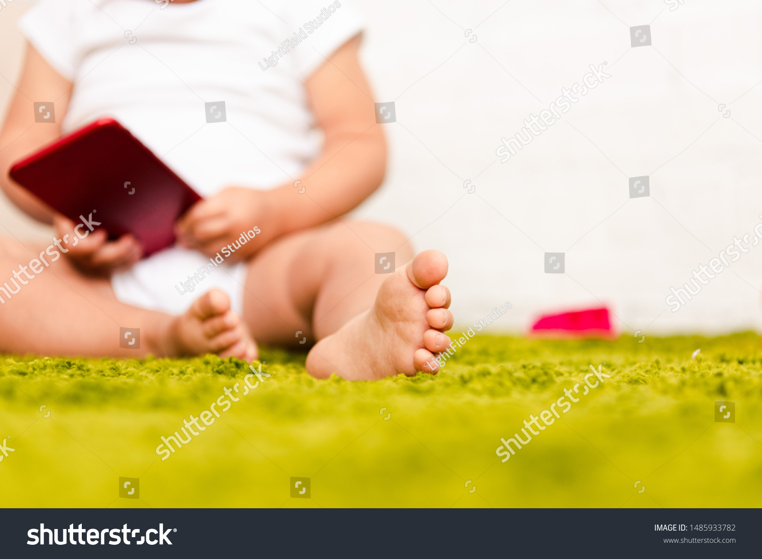 Partial view of little barefoot child sitting on green floor and holding digital device  #1485933782