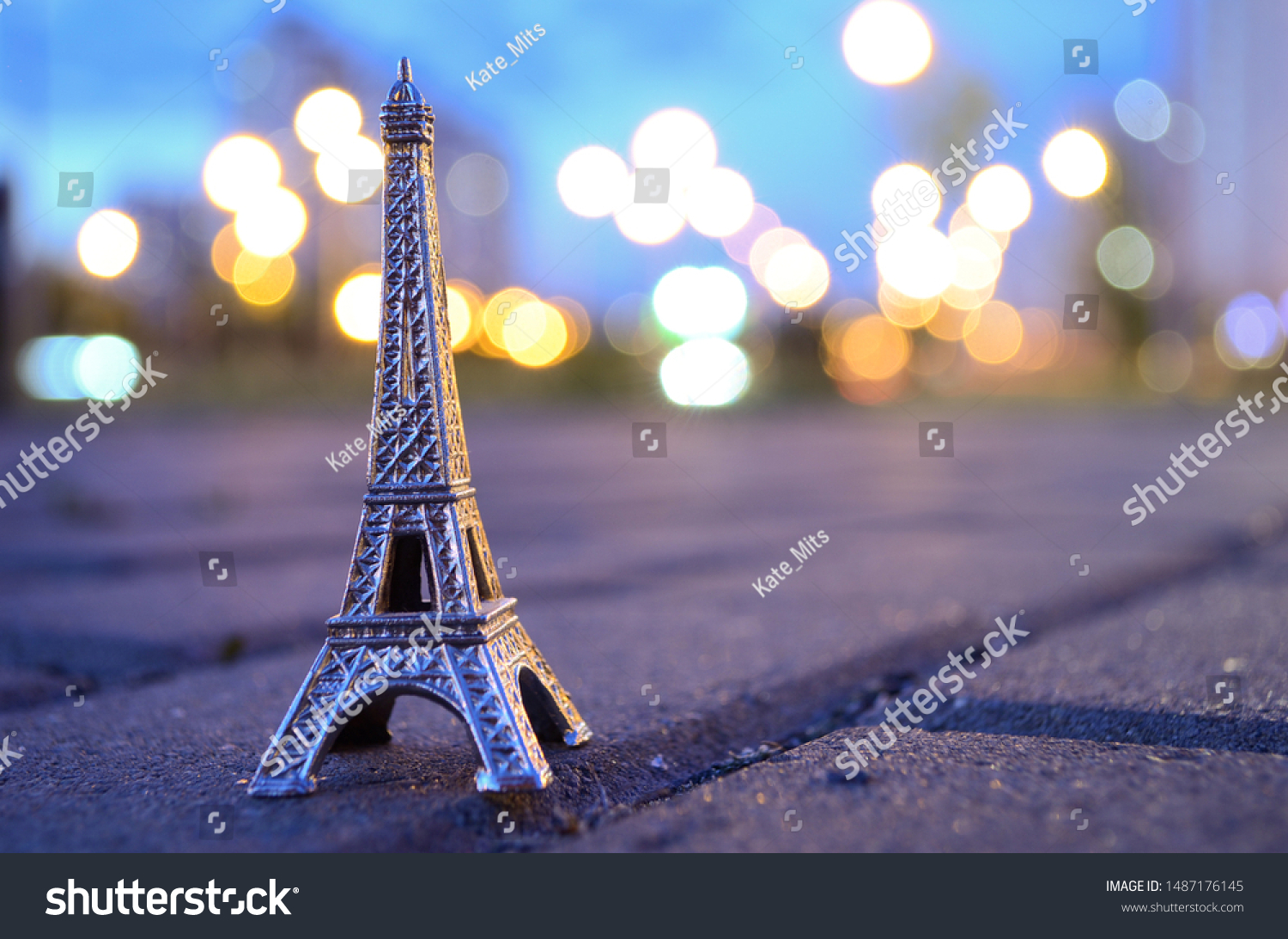 Eiffel tower figure on a background of evening bokeh lights. Located on the paving stones, asphalt. #1487176145
