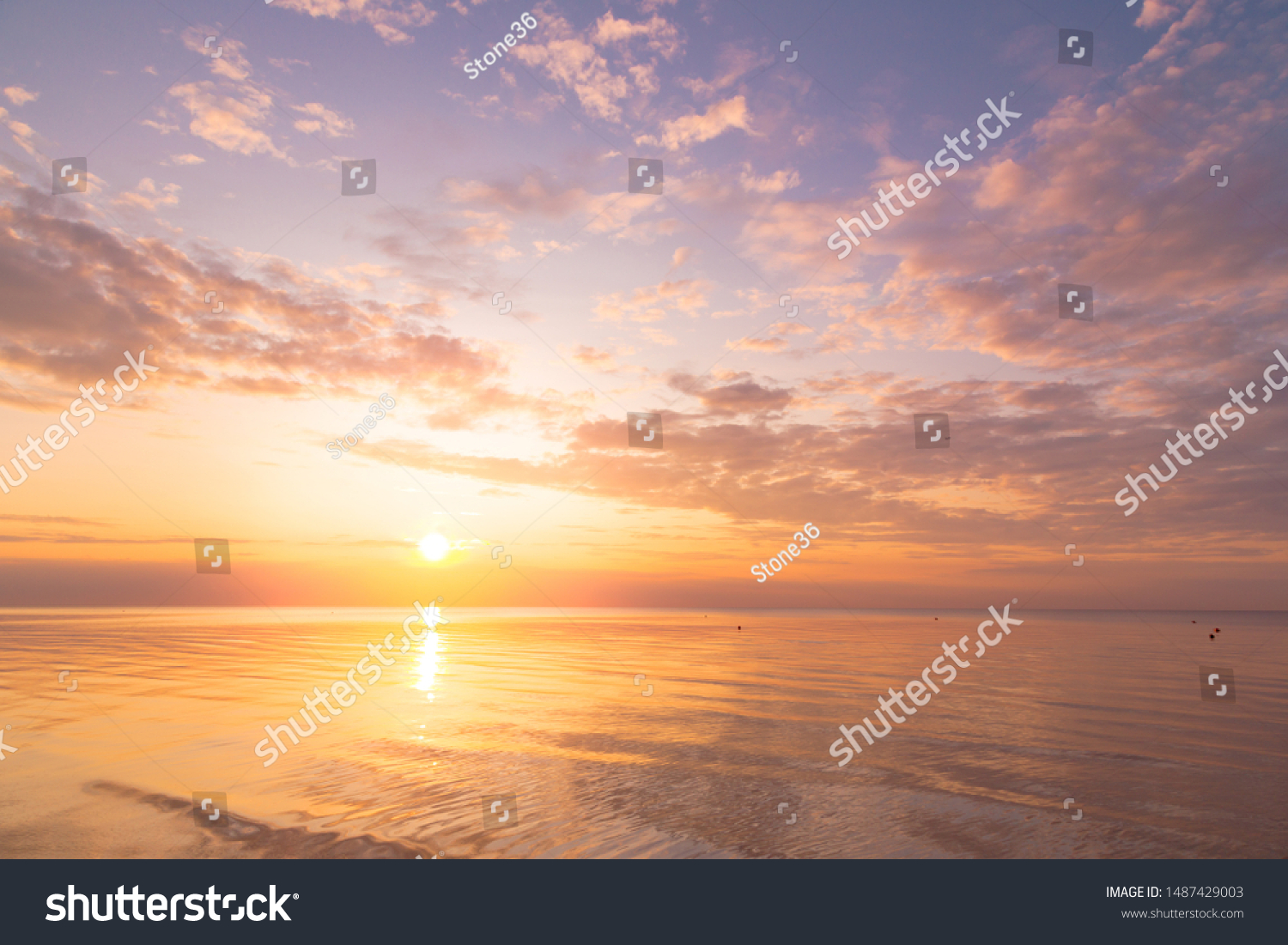 Calm sea with sunset sky and sun through the clouds over. Meditation ocean and sky background. Tranquil seascape. Horizon over the water. #1487429003