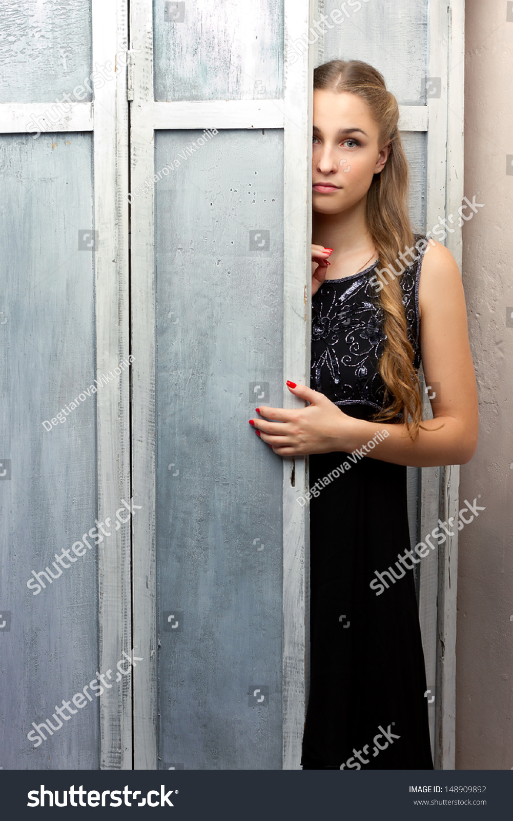girl looks out from behind the cabinet door