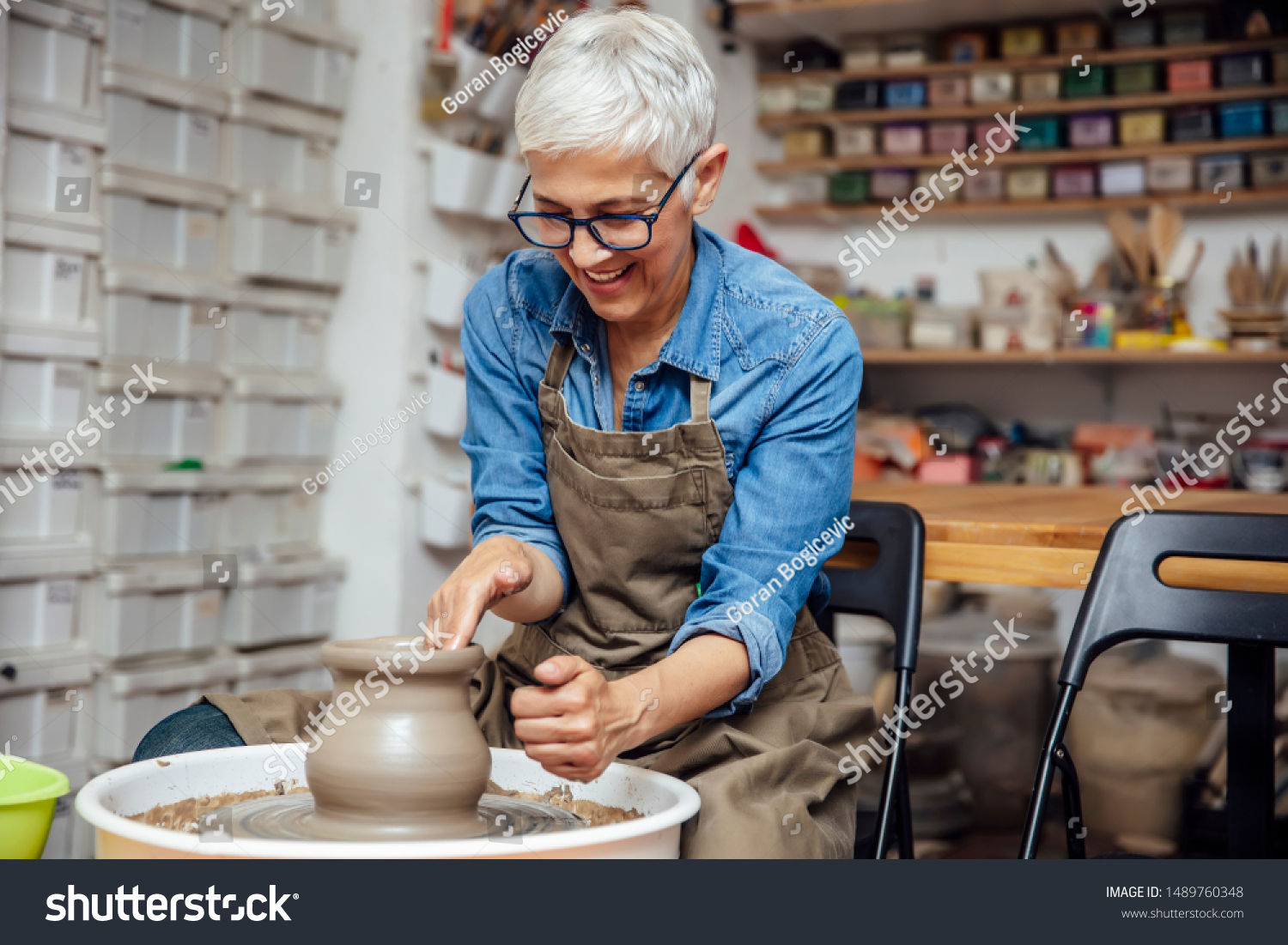 Good looking senior female potter working on pottery wheel while sitting  in her workshop #1489760348