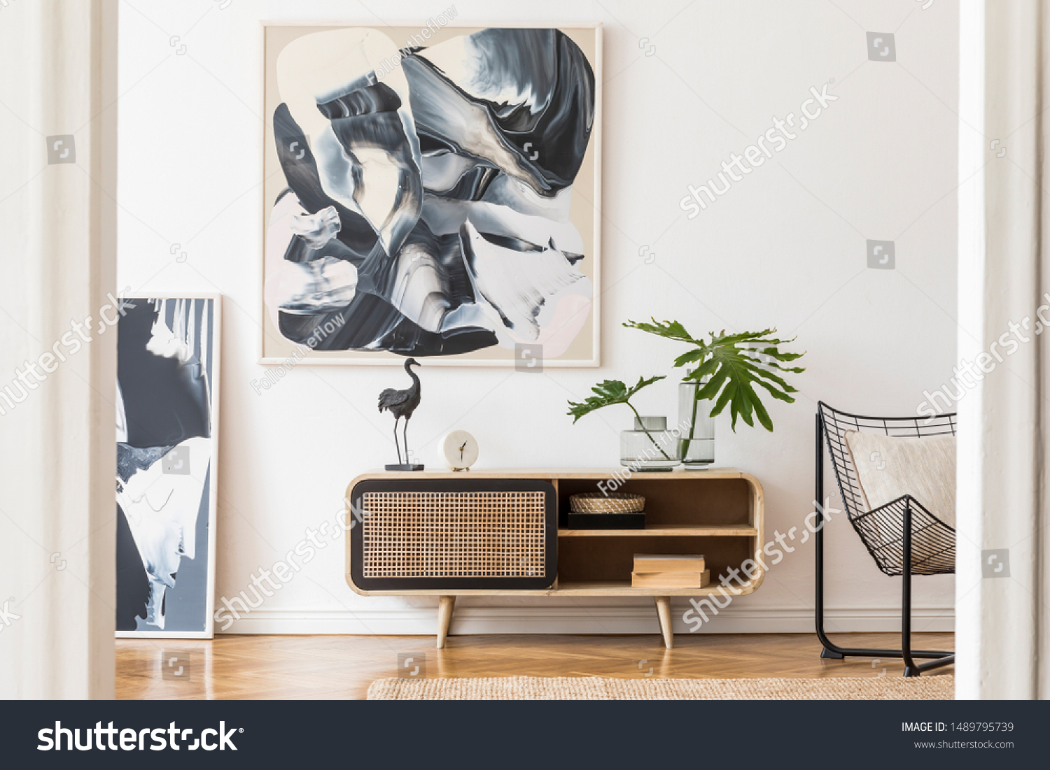 Modern design home interior of living room with wooden commode, design black armchair, tropical leafs and elegant accessories. Stylish home decor. Mock up abstract paintings on the wall. Template. #1489795739