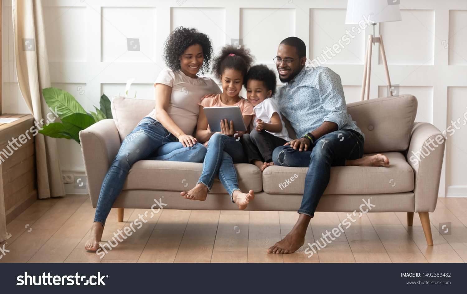 Concept of parental control, modern wireless technology usage, leisure activities at home with children, african full family with daughter and son resting on sofa use tablet computer having fun online