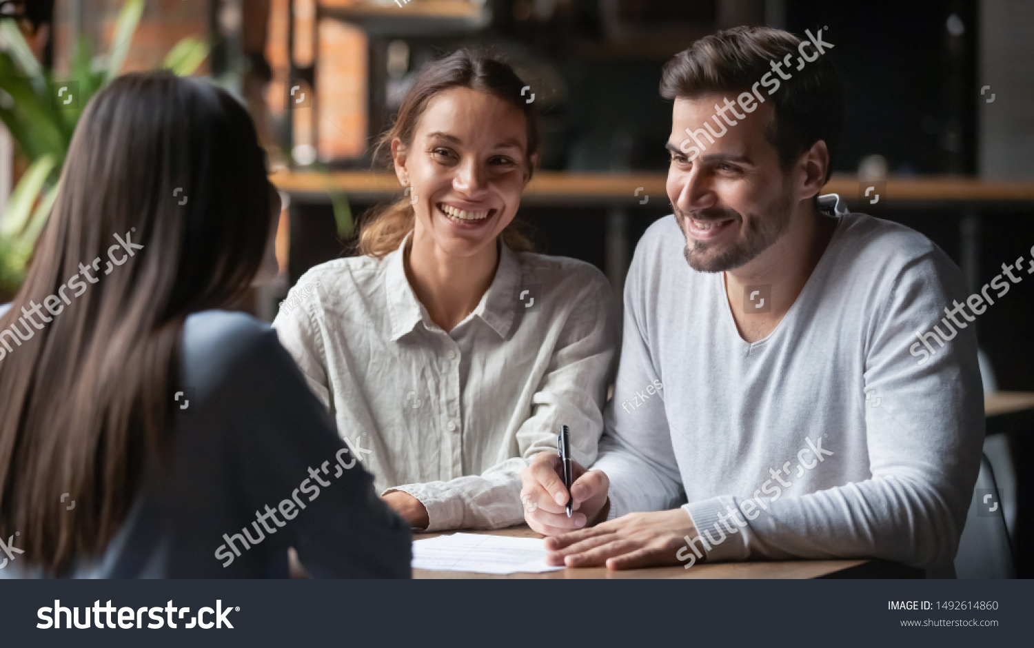 Happy young customers couple ready to sign bank loan agreement meeting broker agent, smiling husband and wife consider finance investing insurance contract deal decide on lease offer listen insurer #1492614860