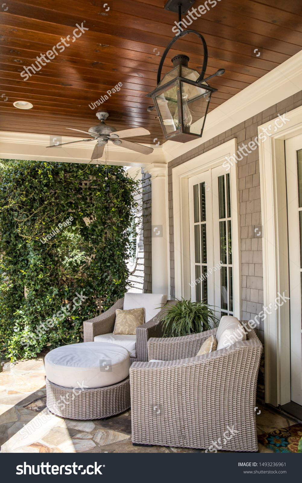 outdoor patio porch of traditional upgraded custom home with seating for entertaining and dining with hanging lanterns  #1493236961